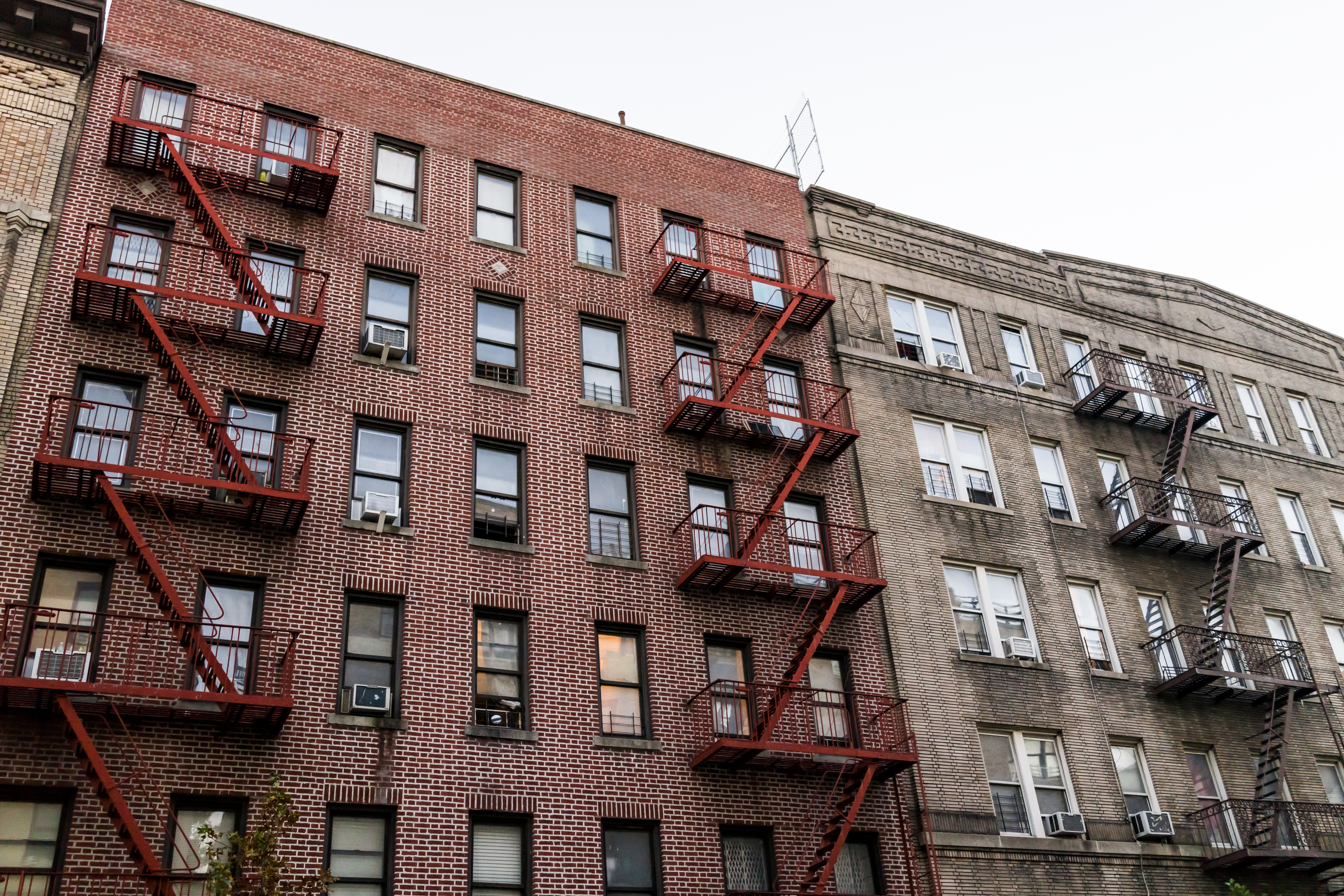 Two NYC tenement buildings next to each other with several fire escapes.