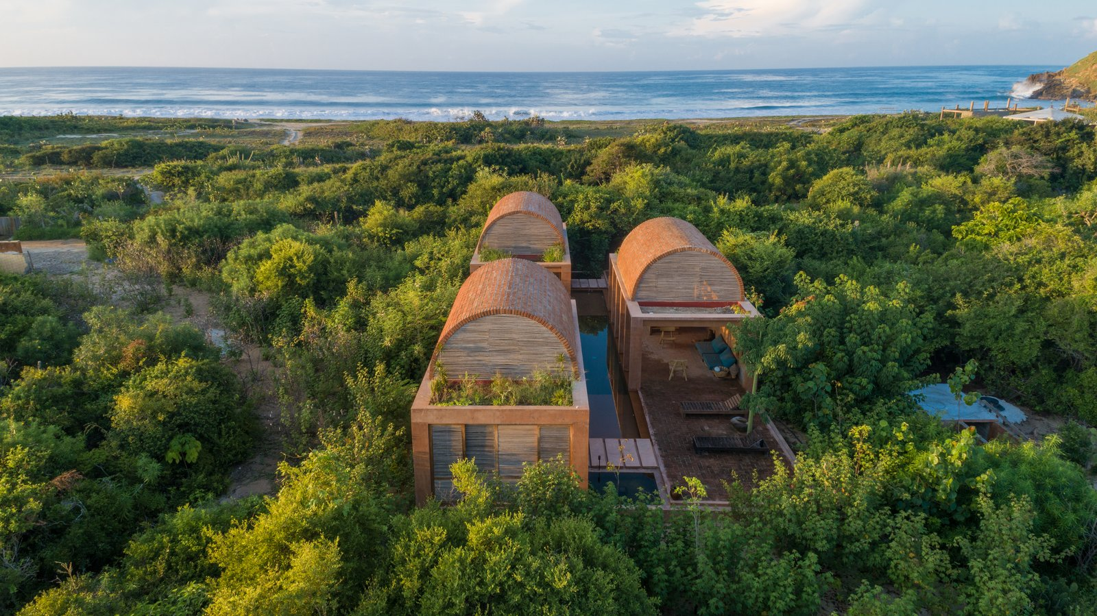 A vaulted brick house features three different arched roofs set inside a dense forest. In the distance you can see the ocean.