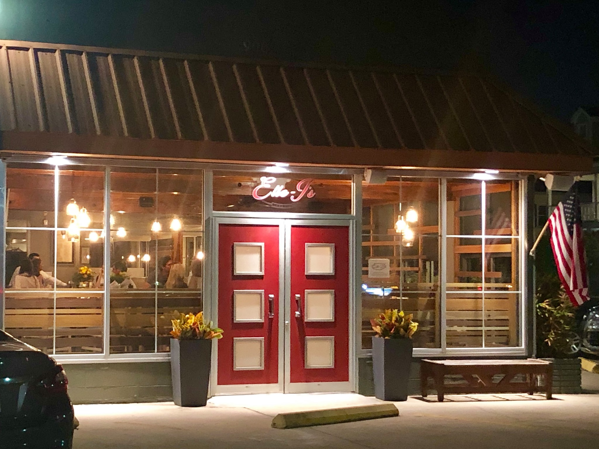 The exterior of a restaurant with glass window walls, a slate roof, and red doors