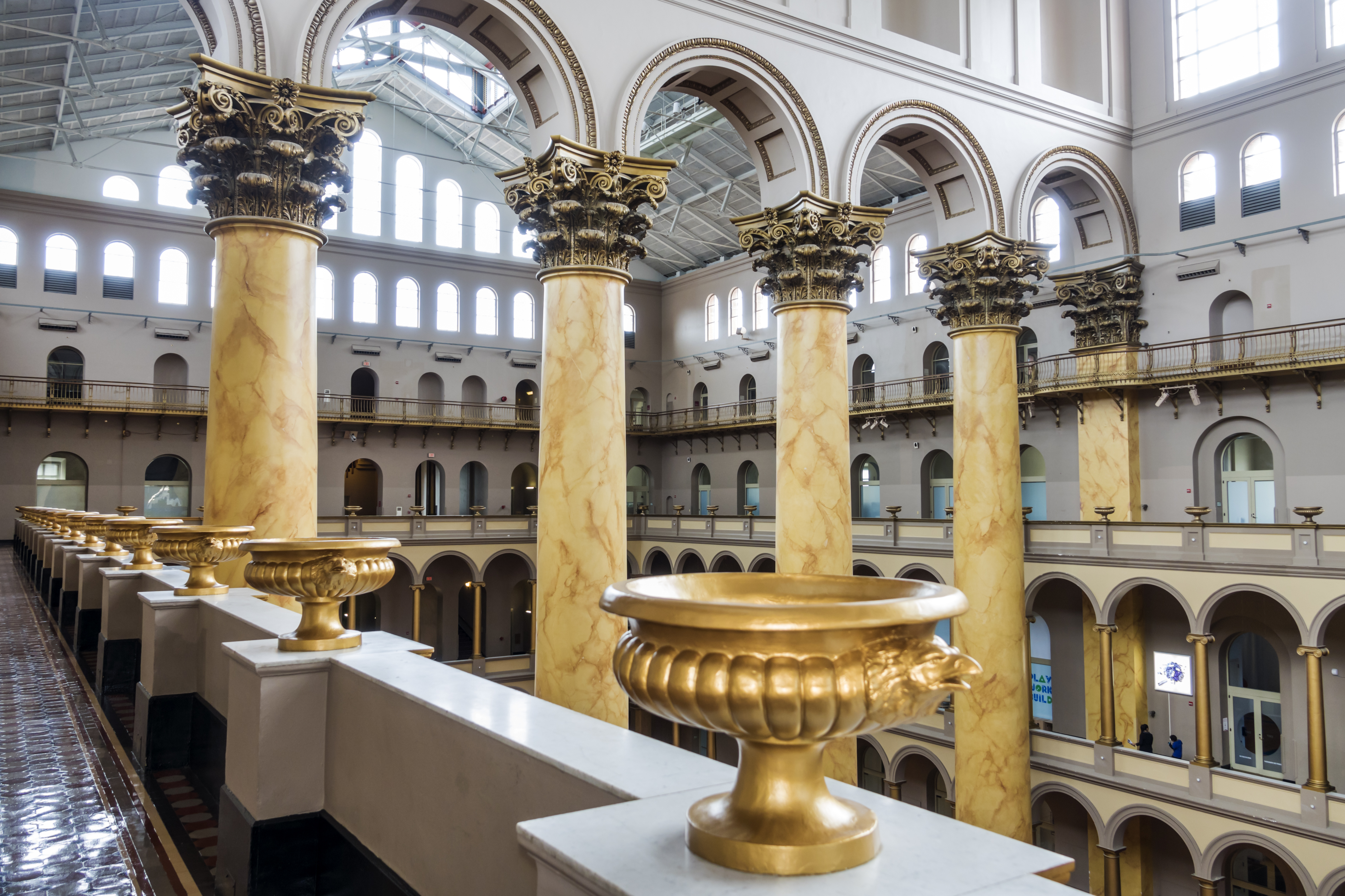 A row of Corinthian columns inside a grand romanesque building. There are gold urns along a balcony.