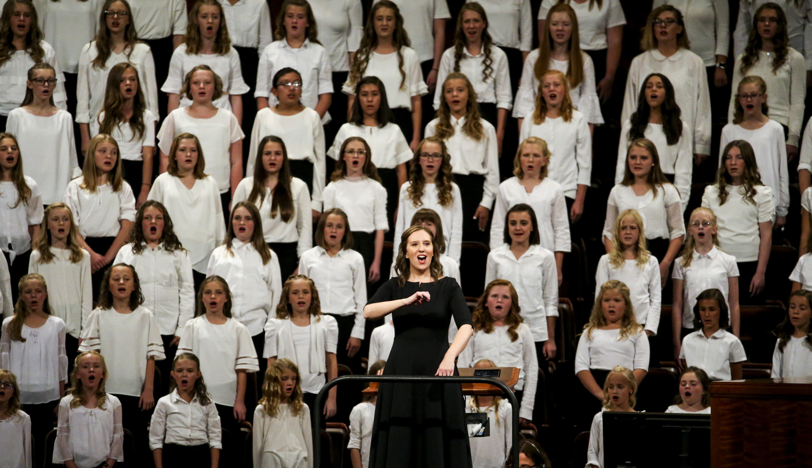 Kasey Bradbury, choir director, leads the audience in a hymn while the choir of Primary girls and young women from stakes in West Jordan sings behind her during the women's session of the 189th Semiannual General Conference of The Church of Jesus Christ of Latter-day Saints at the Conference Center in Salt Lake City on Saturday, Oct. 5, 2019.