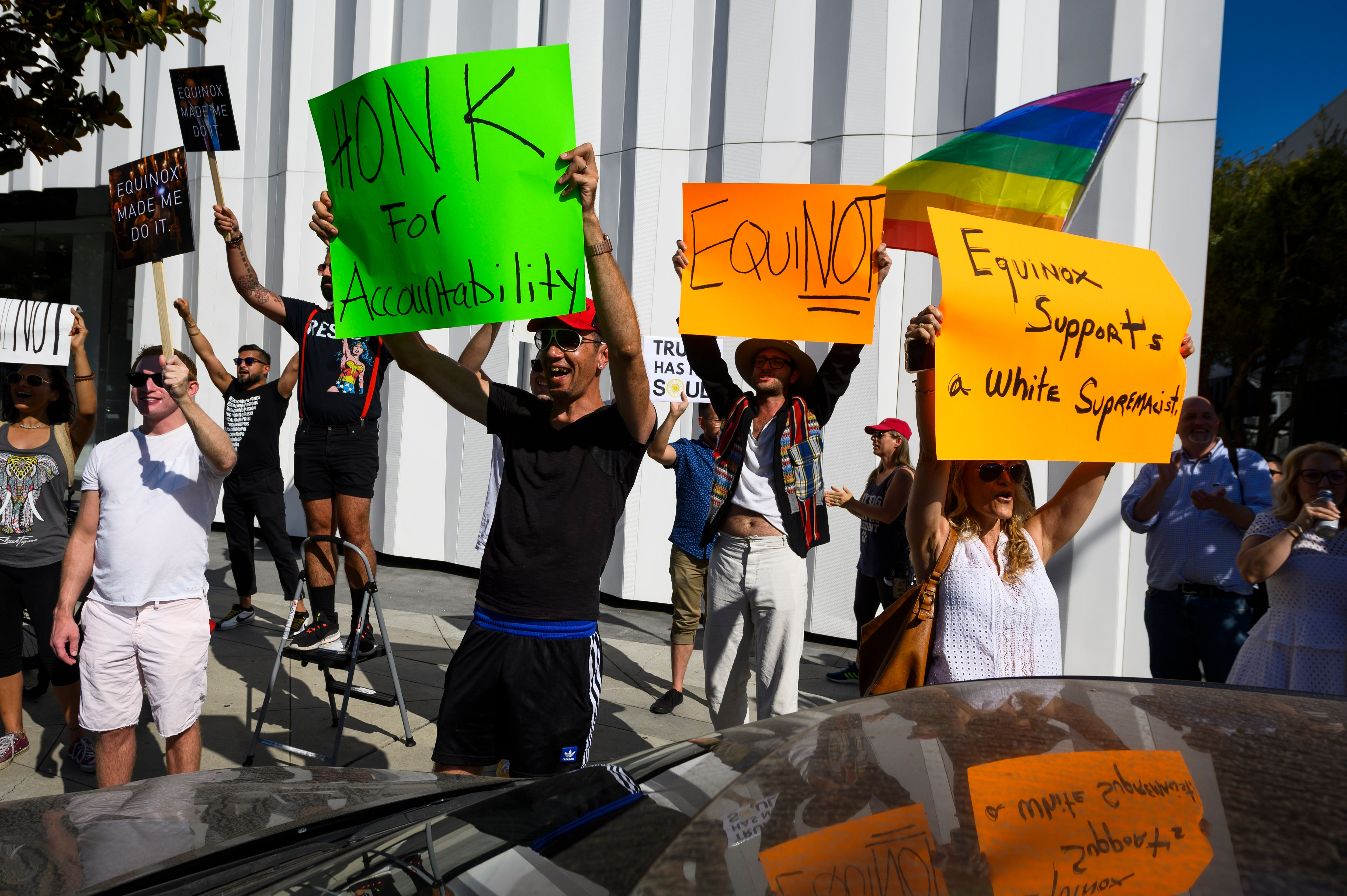 """Protesters hold signs that read, """"Honk for accountability,"""" """"EquiNOT,"""" and, """"Equinox supports a white supremacist."""""""