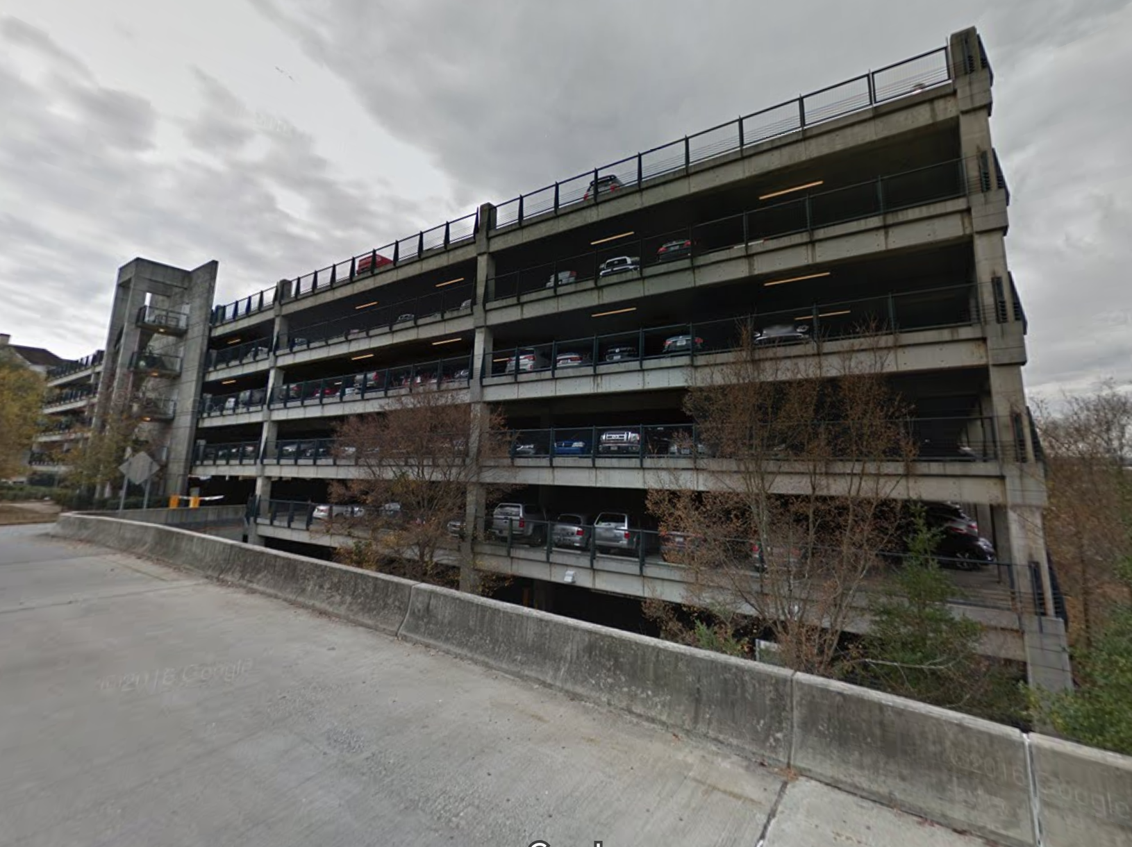 A large parking deck is filled with cars.