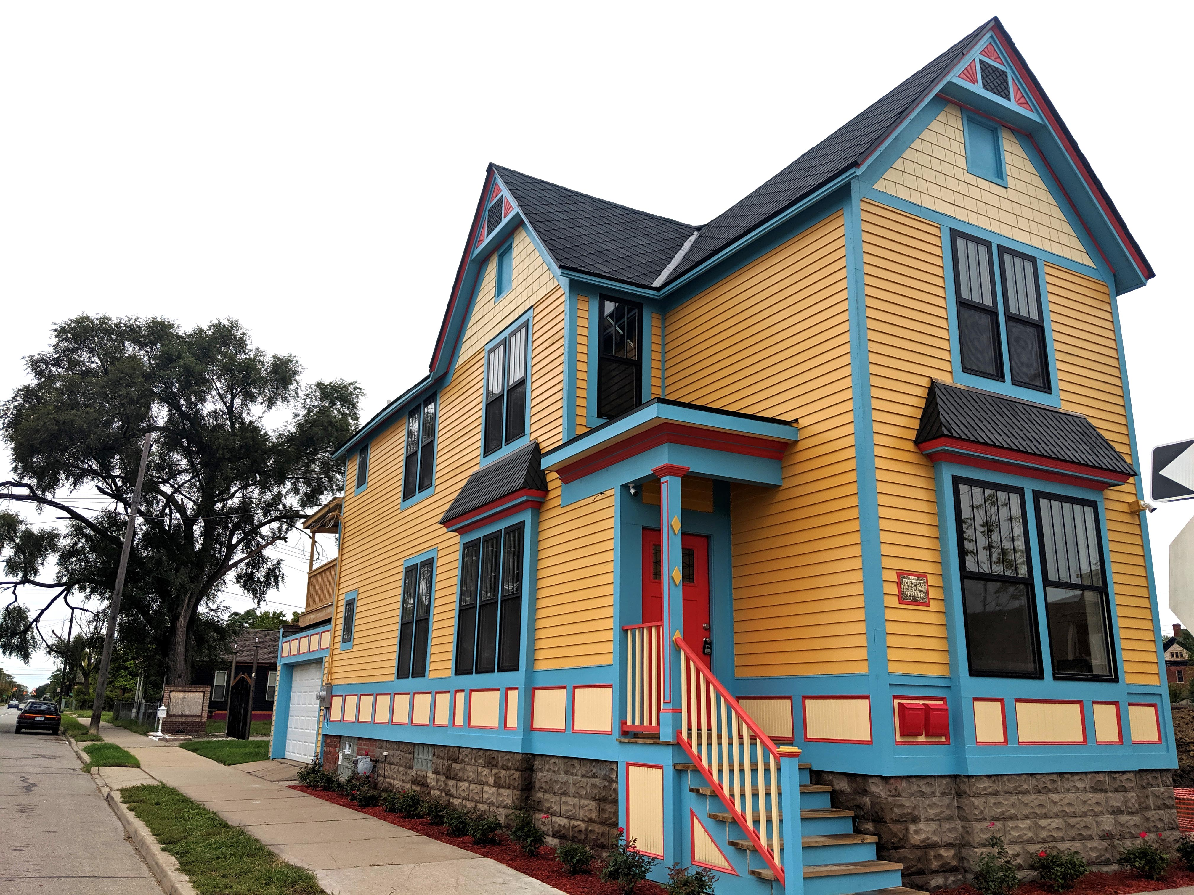 A colorfully-painted three-story home with yellow siding and blue trim. There's two gables on the front and side.