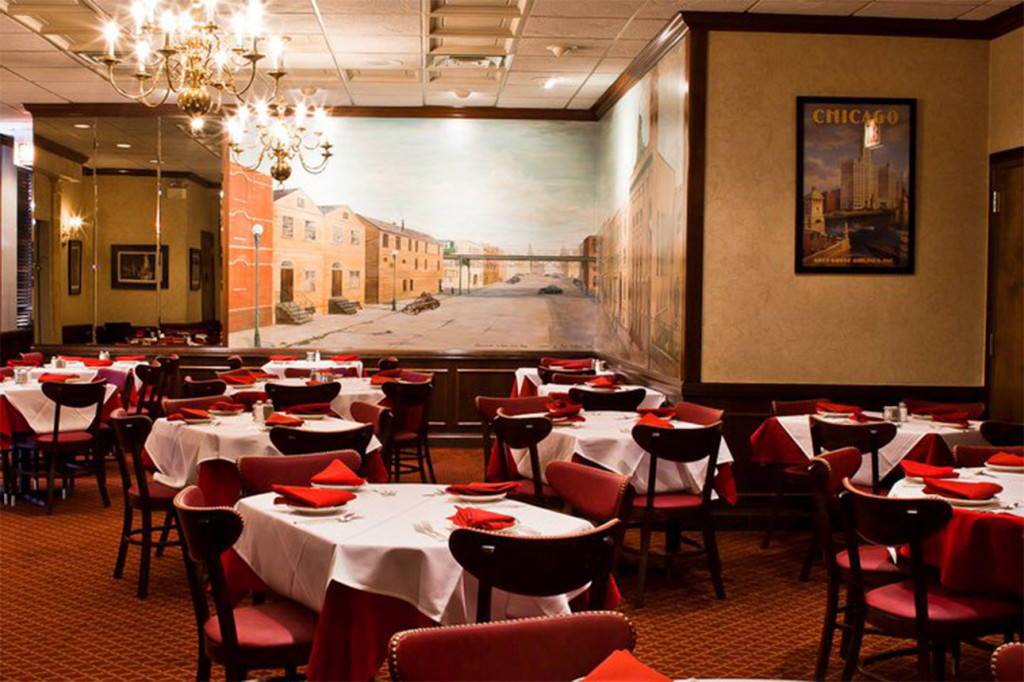 Gene & Georgetti's dining room has red tables and chairs with white tablecloths and a throwback mural of a Chicago street corner.