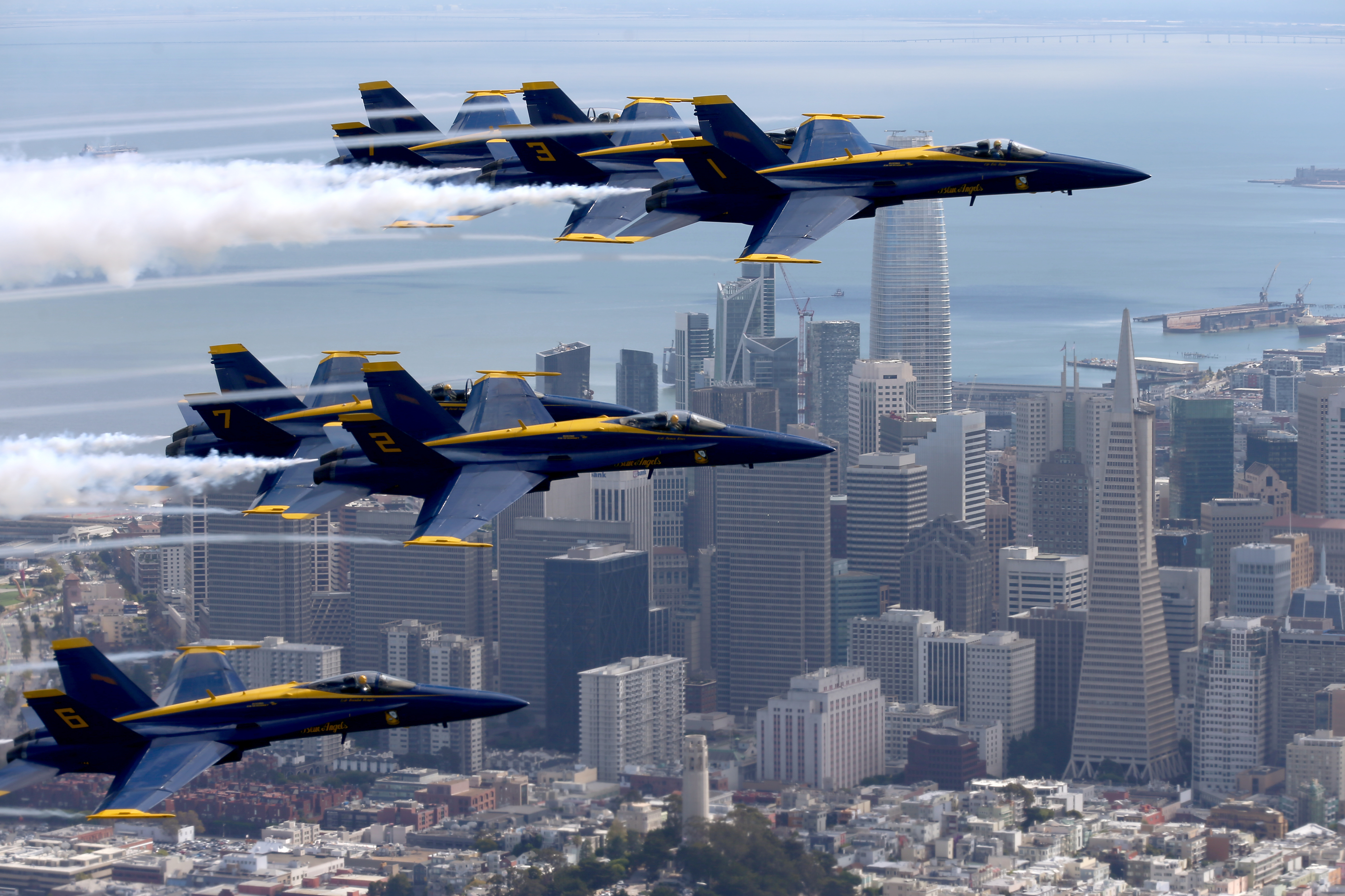 Close-up of blue and yellow fighter jets flying over San Francisco, with tall buildings and the bay below.