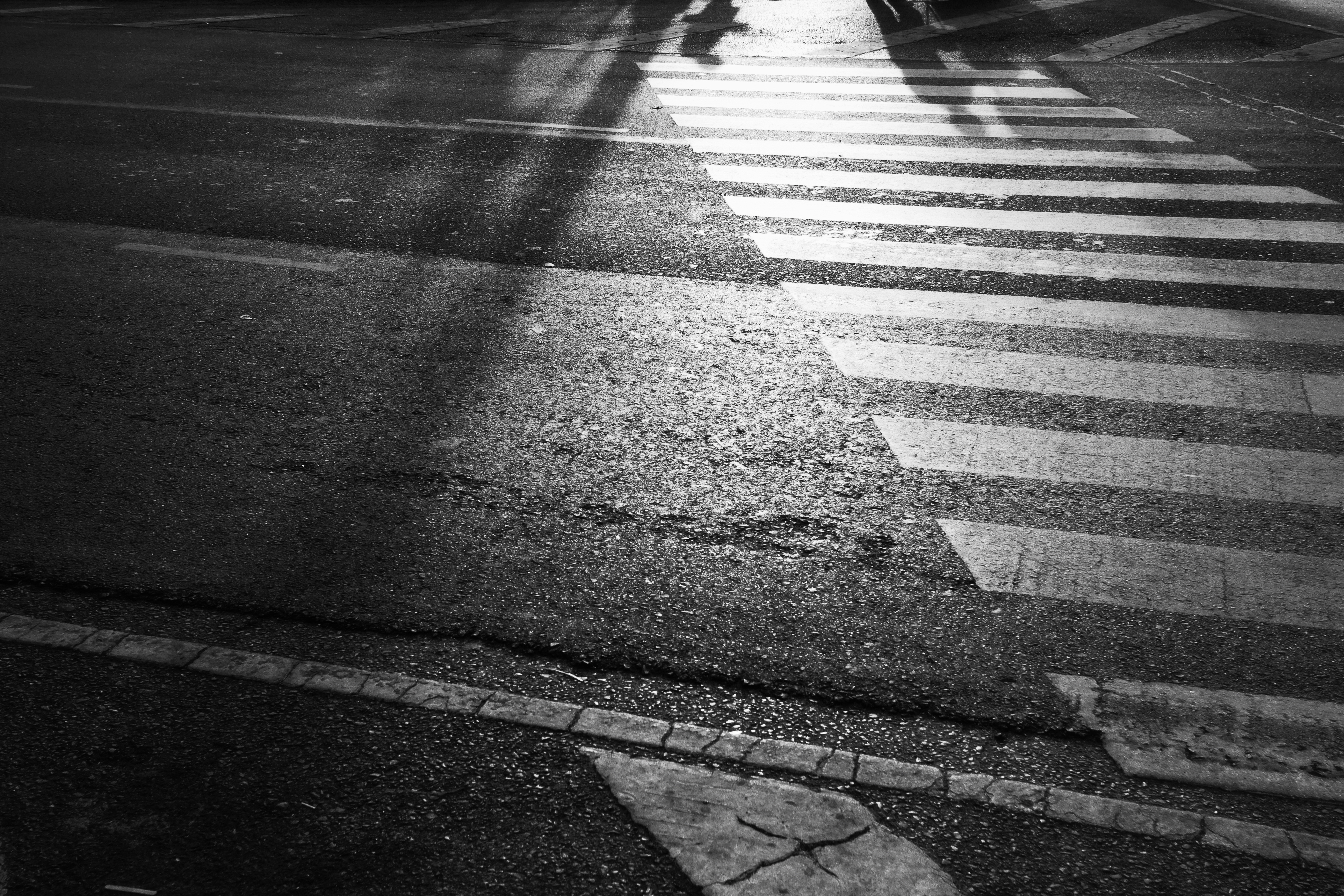 A black-and-white photo of a crosswalk and a road.