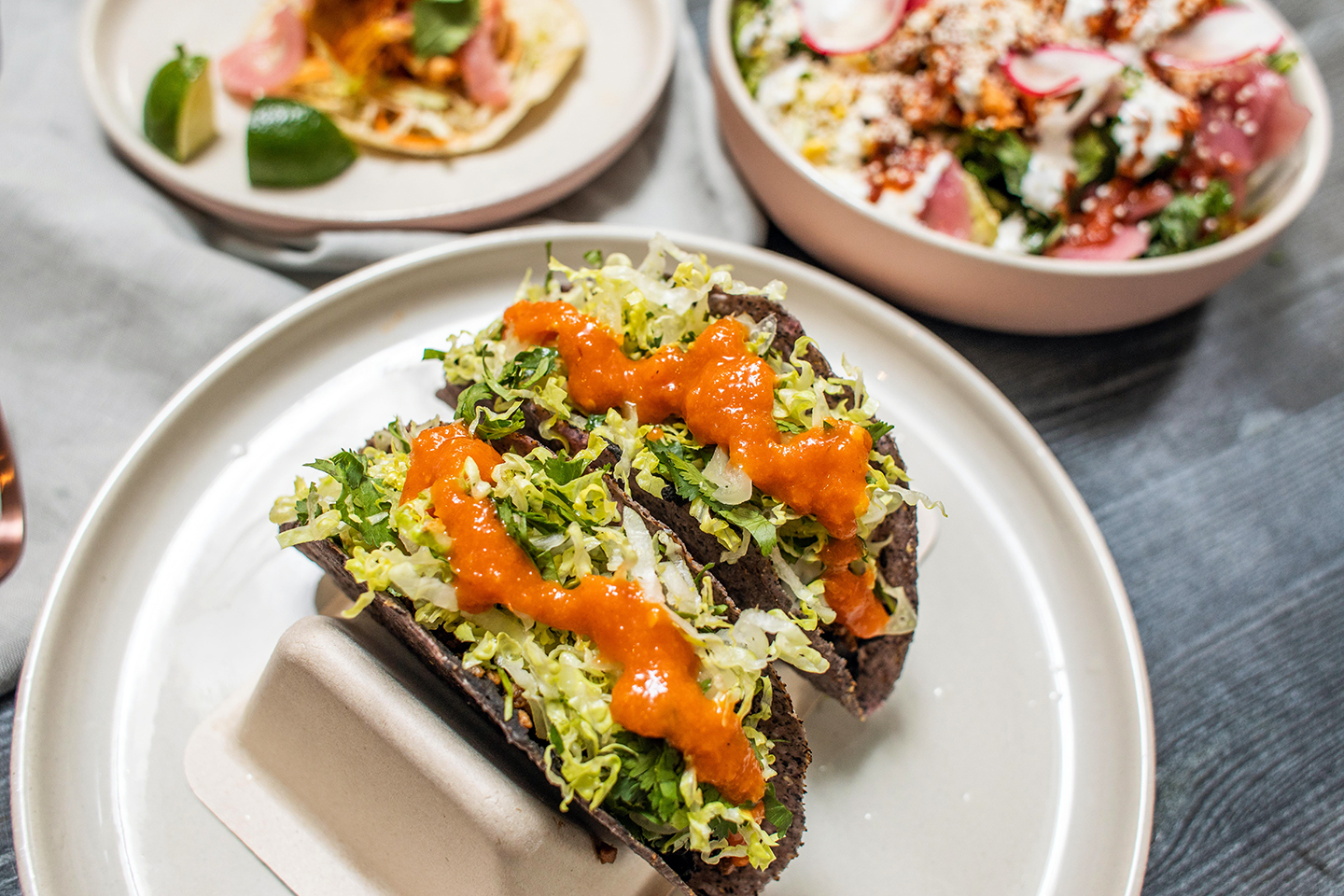 Two tacos sit side-by-side on a plate, topped with lettuce and sauce, with a blurry plated taco in the background