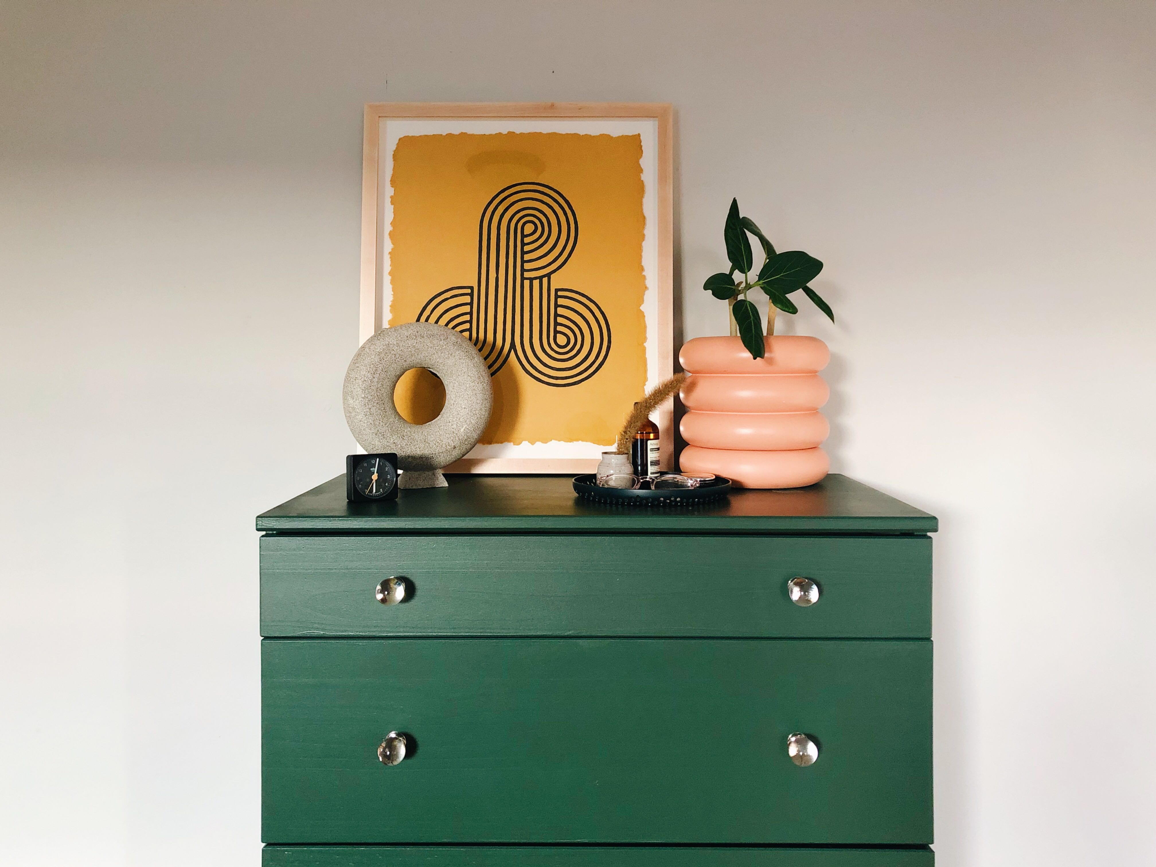 A dark green dresser with a pink planter and yellow framed print on top of it.
