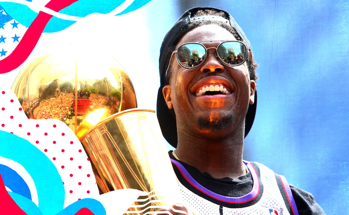 Kyle Lowry smiles while holding the championship trophy during the Raptors' title parade.
