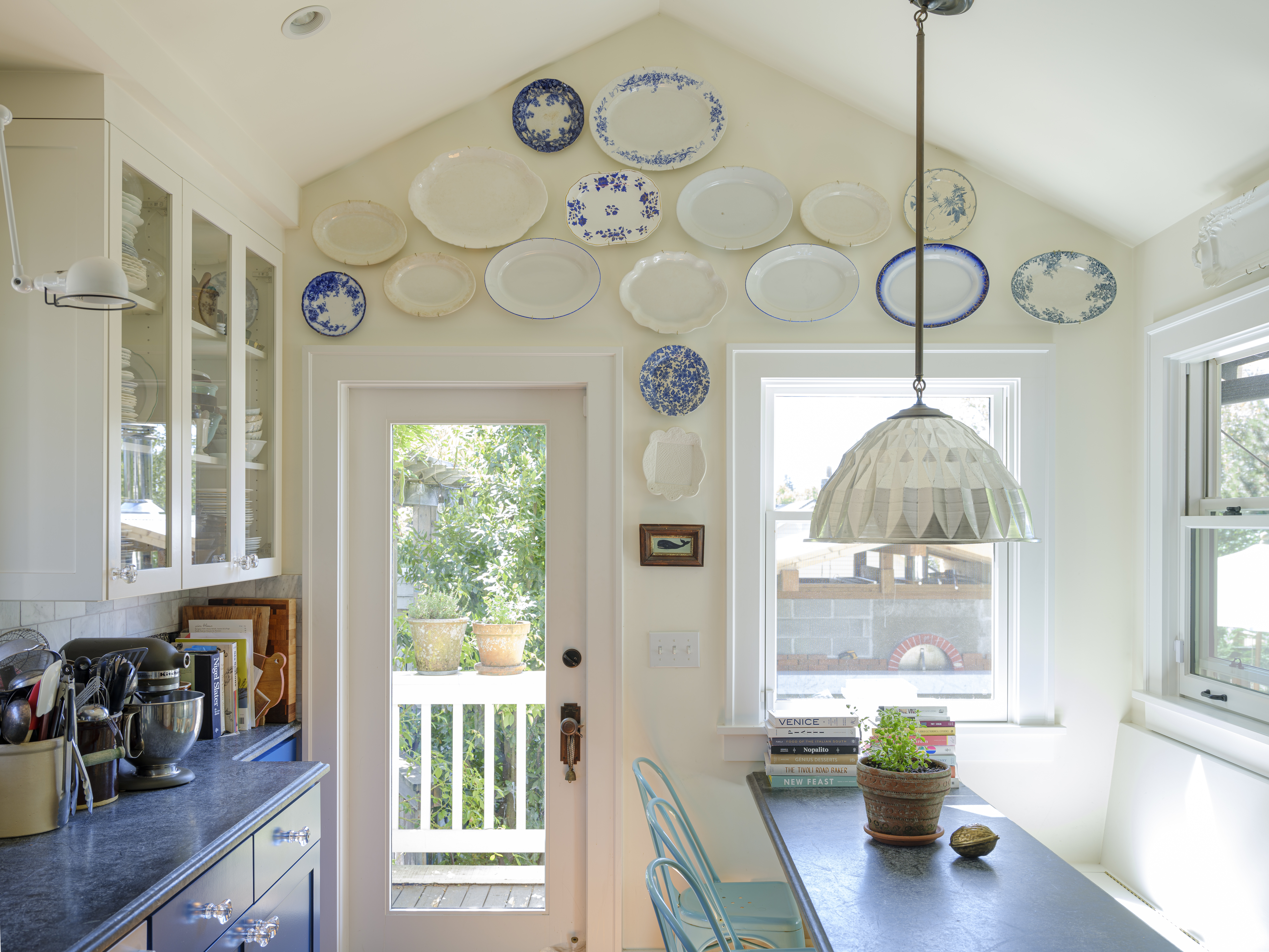 A kitchen and dining area. There is a table, chairs, blue cabinetry, cupboards with glass doors, and a hanging light fixture. On the wall hanging above a door are multiple assorted plates.