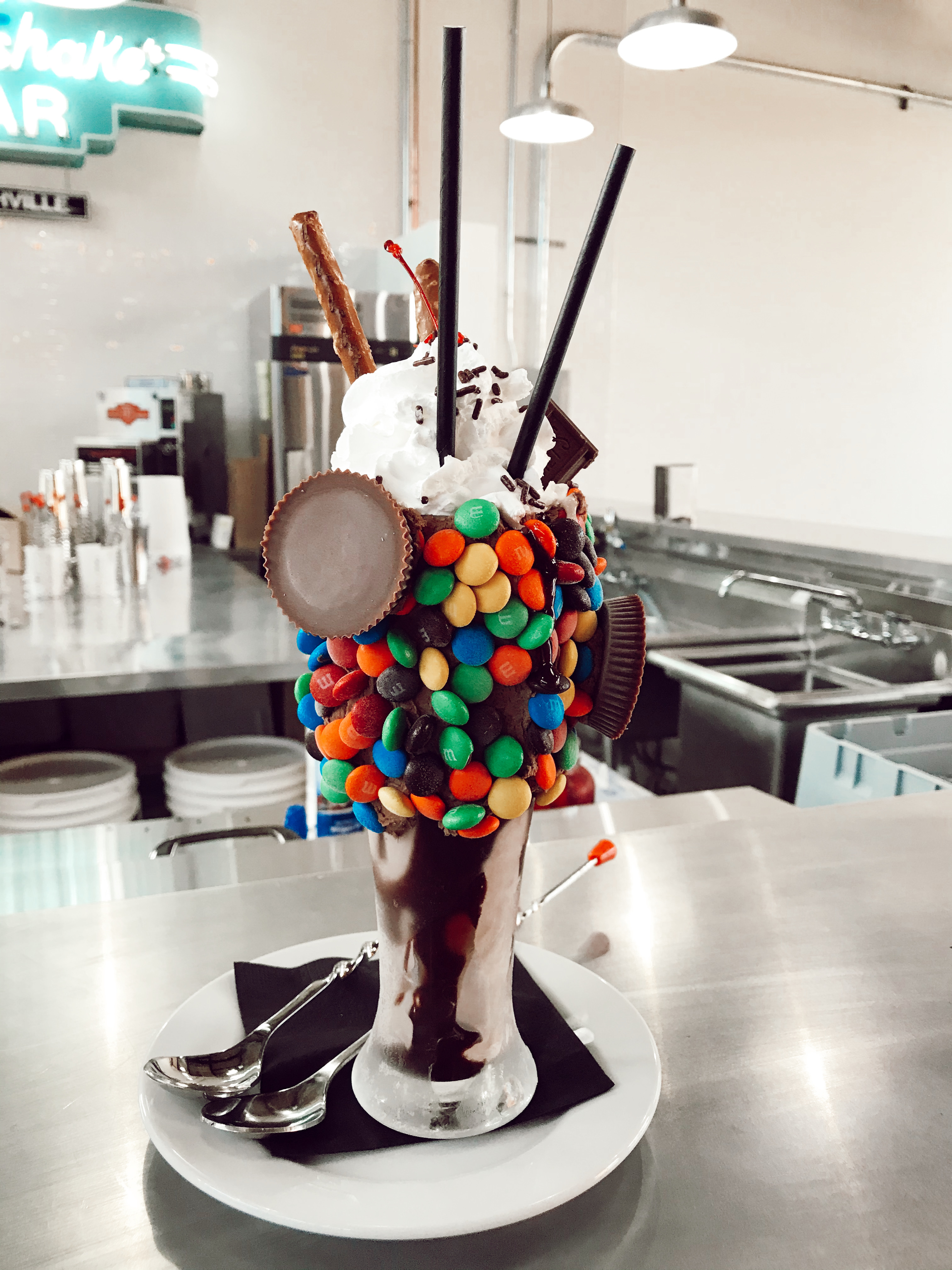 a milkshake in a glass cup covered with brightly colored candy, peanut butter cups, and whipped cream