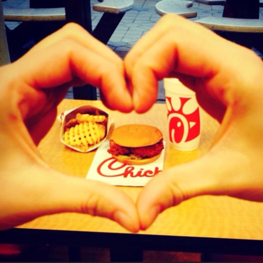 "A Chick-fil-A chicken sandwich and waffle fries seen through an Instagrammer's ""heart hands"" pose."