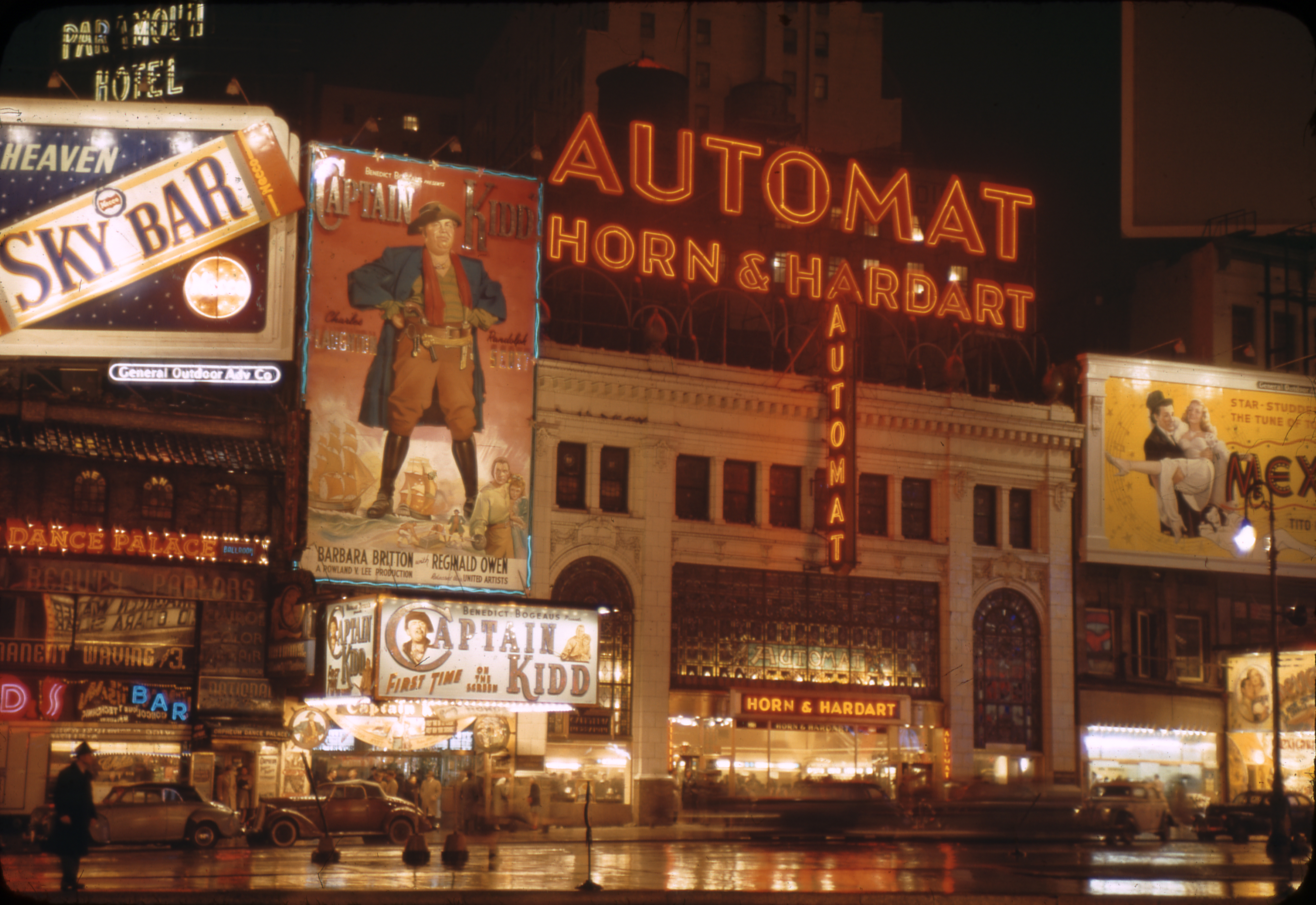 A neon sign advertising a Horn and Hardart automat glows orange in the night in busy Times Square in the 1940s.