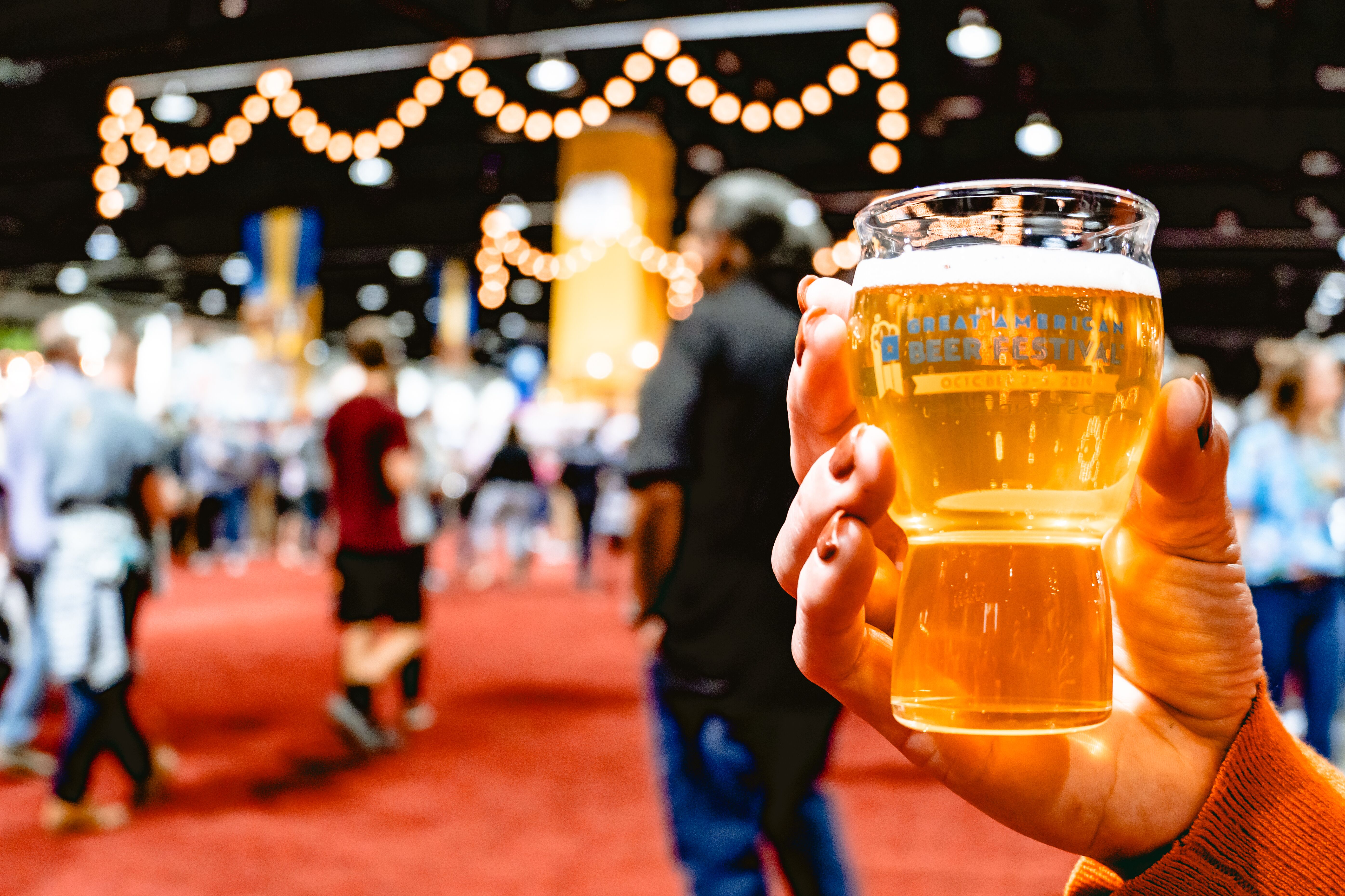 A close-up photo of a hand holding a souvenir tasting glass that has been filled with golden beer at the Great American Beer Festival.