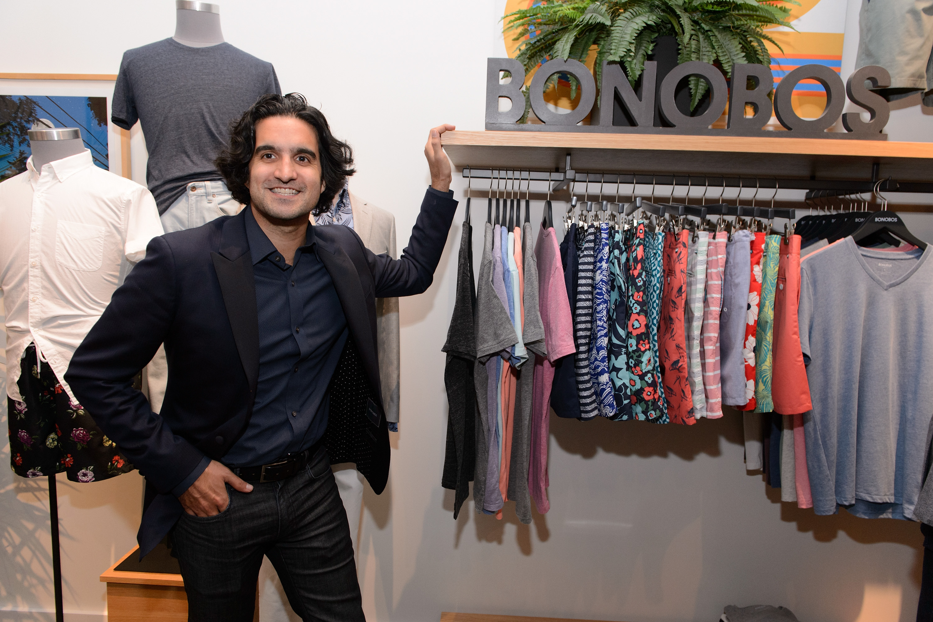 Bonobos founder Andy Dunn poses while leaning against a store's clothing rack.