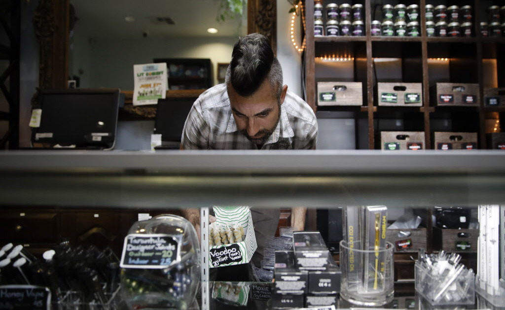 Jerred Kiloh, owner of the Higher Path medical marijuana dispensary, stocks shelves with with cannabis products in Los Angeles.