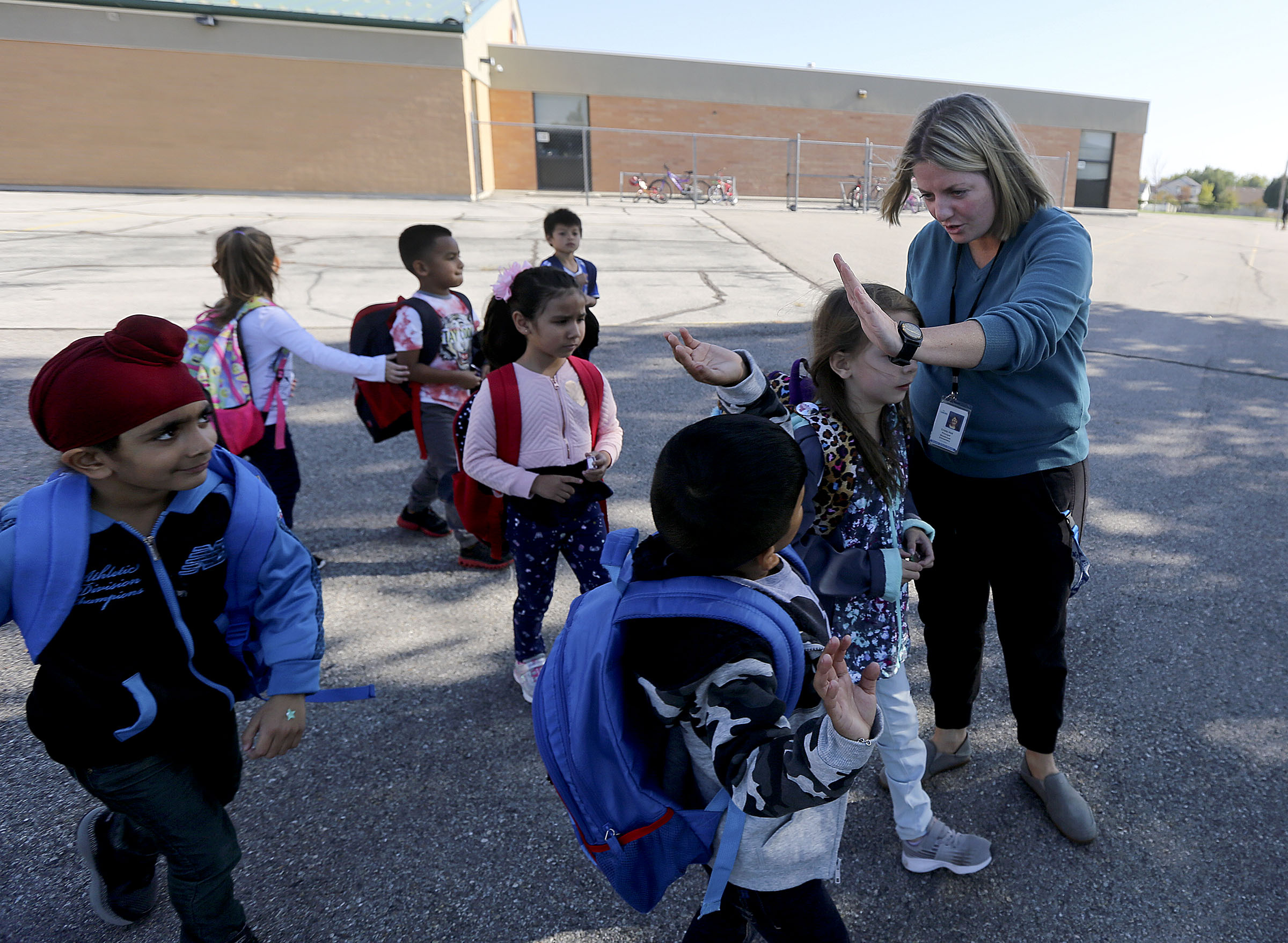 Westbrook Elementary School Principal Crista Holt high-fives students as they leave the Taylorsville school on Monday, Oct. 7, 2019. Granite Board of Education will vote in November on whether or not to close Westbrook as well as Sandberg Elementary School in West Valley City.
