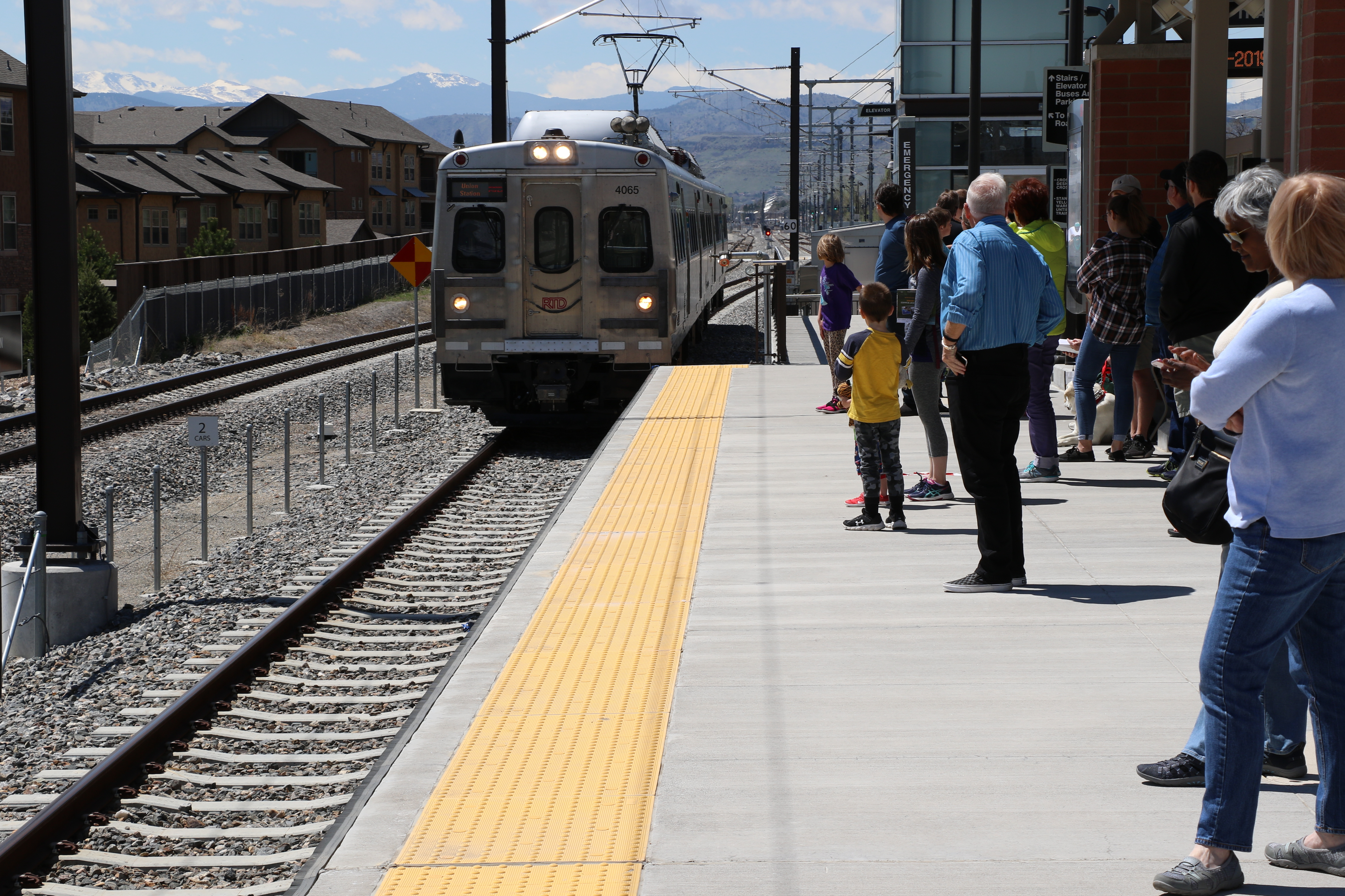 A commuter rail train pulls into the station as riders gather near the platform edge. Mountains stand in the background.