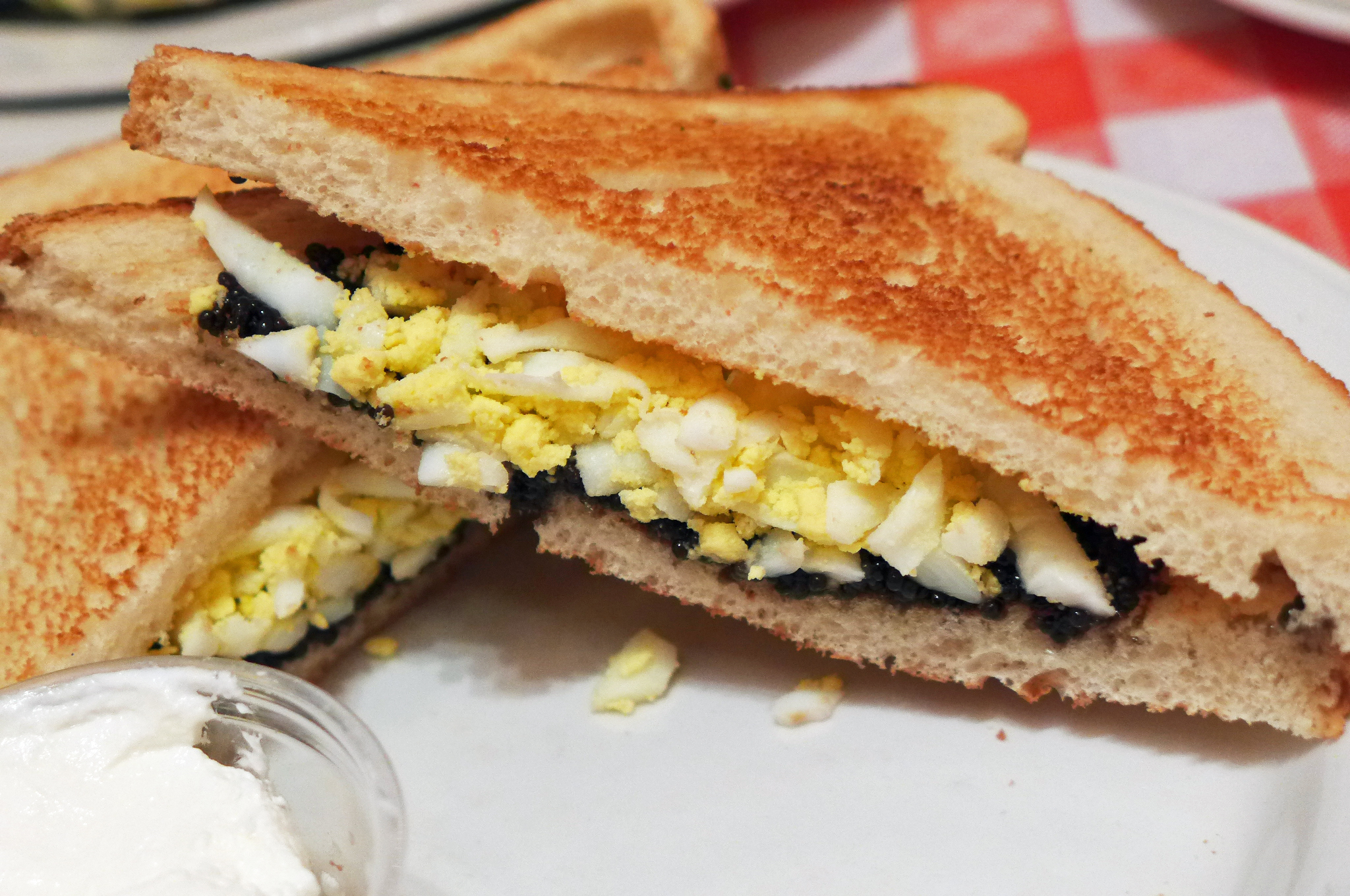 A sandwich cut in half on toasted white bread filled with shredded boiled eggs and black caviar...