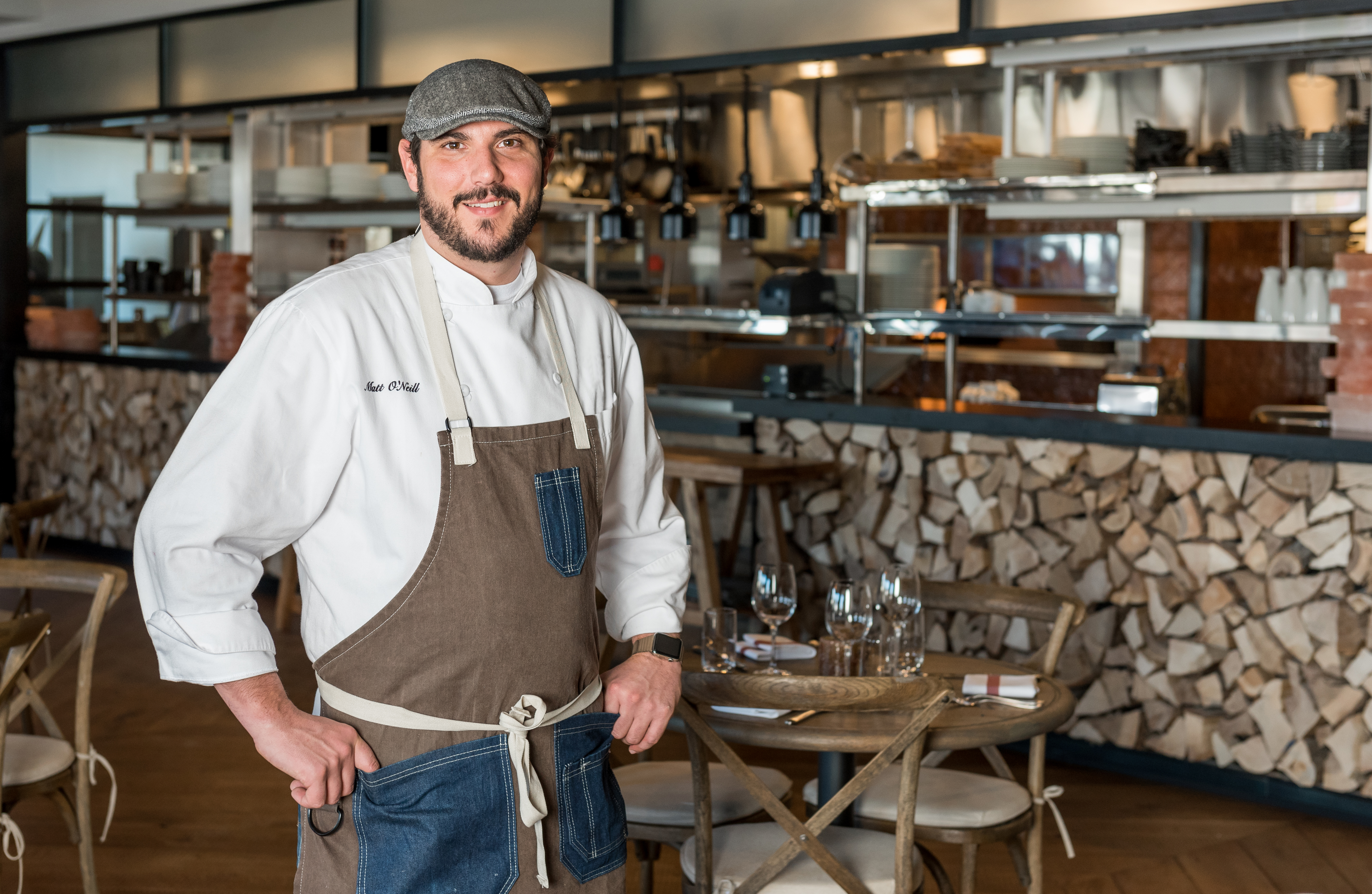 A white man in a white chef's coat stands in front of an open kitchen.