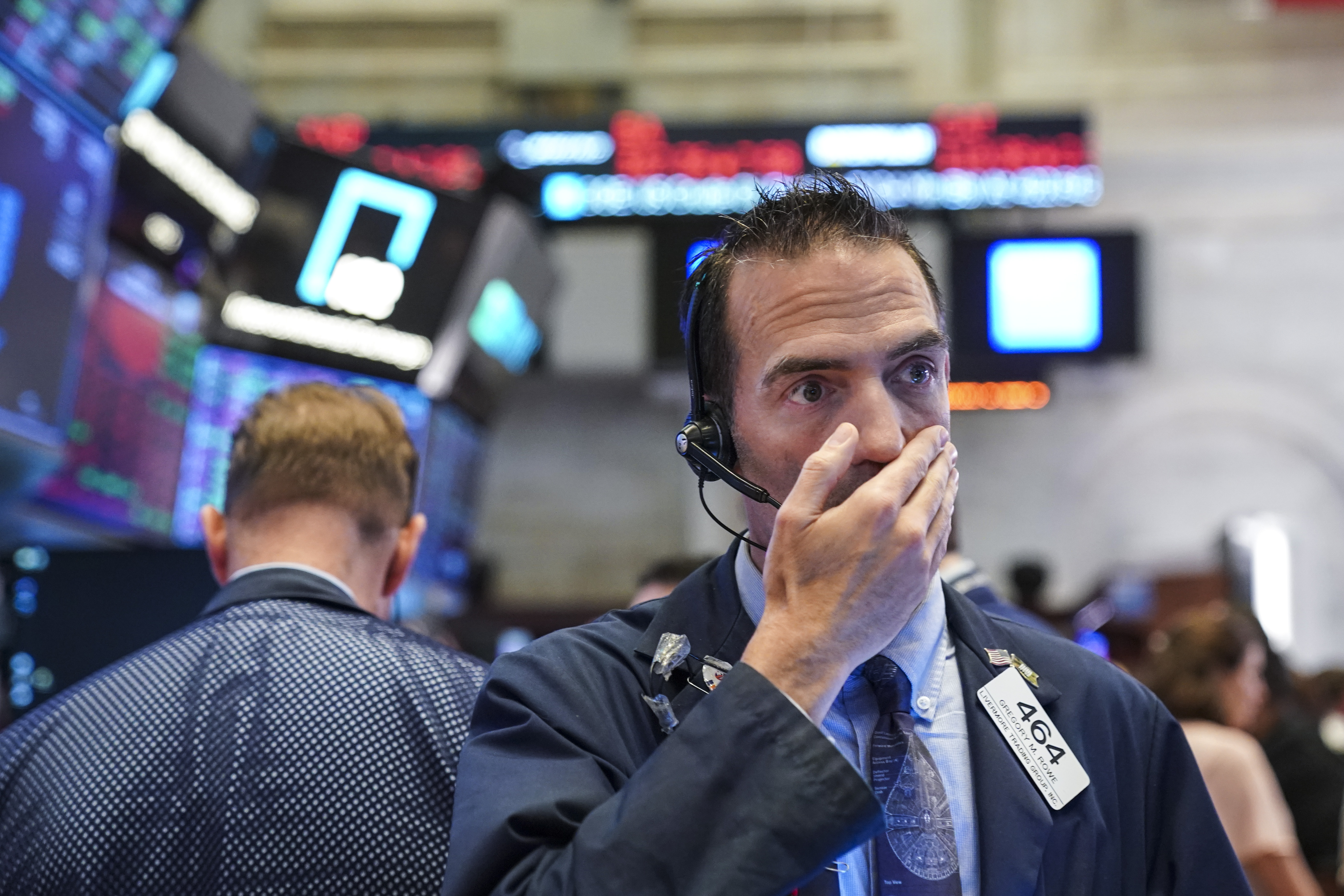 A trader on the stock exchange floor with his hand over his mouth.