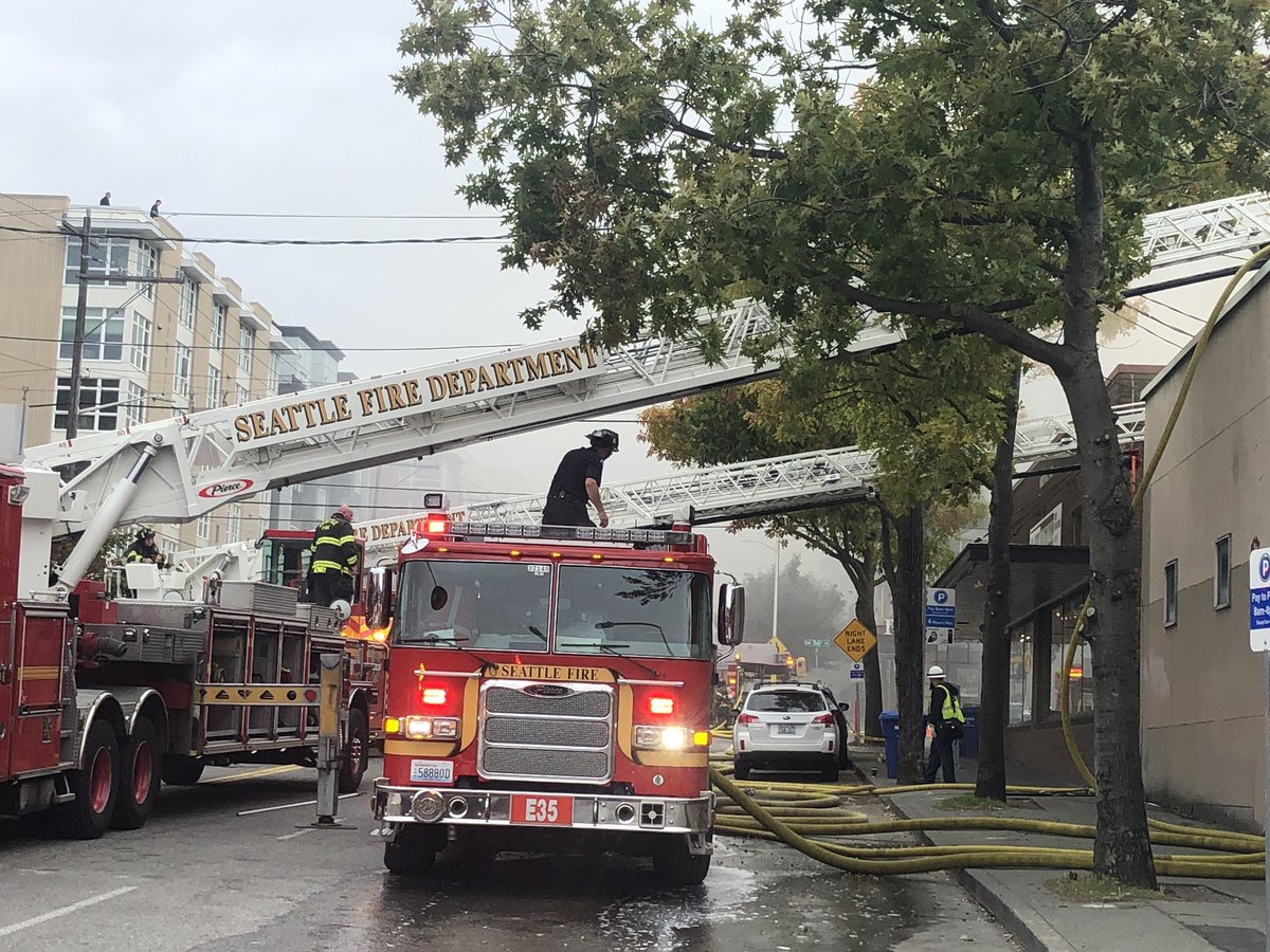A view of a Seattle fire truck responding to a blaze on Market Street in Ballard with ladder raised.