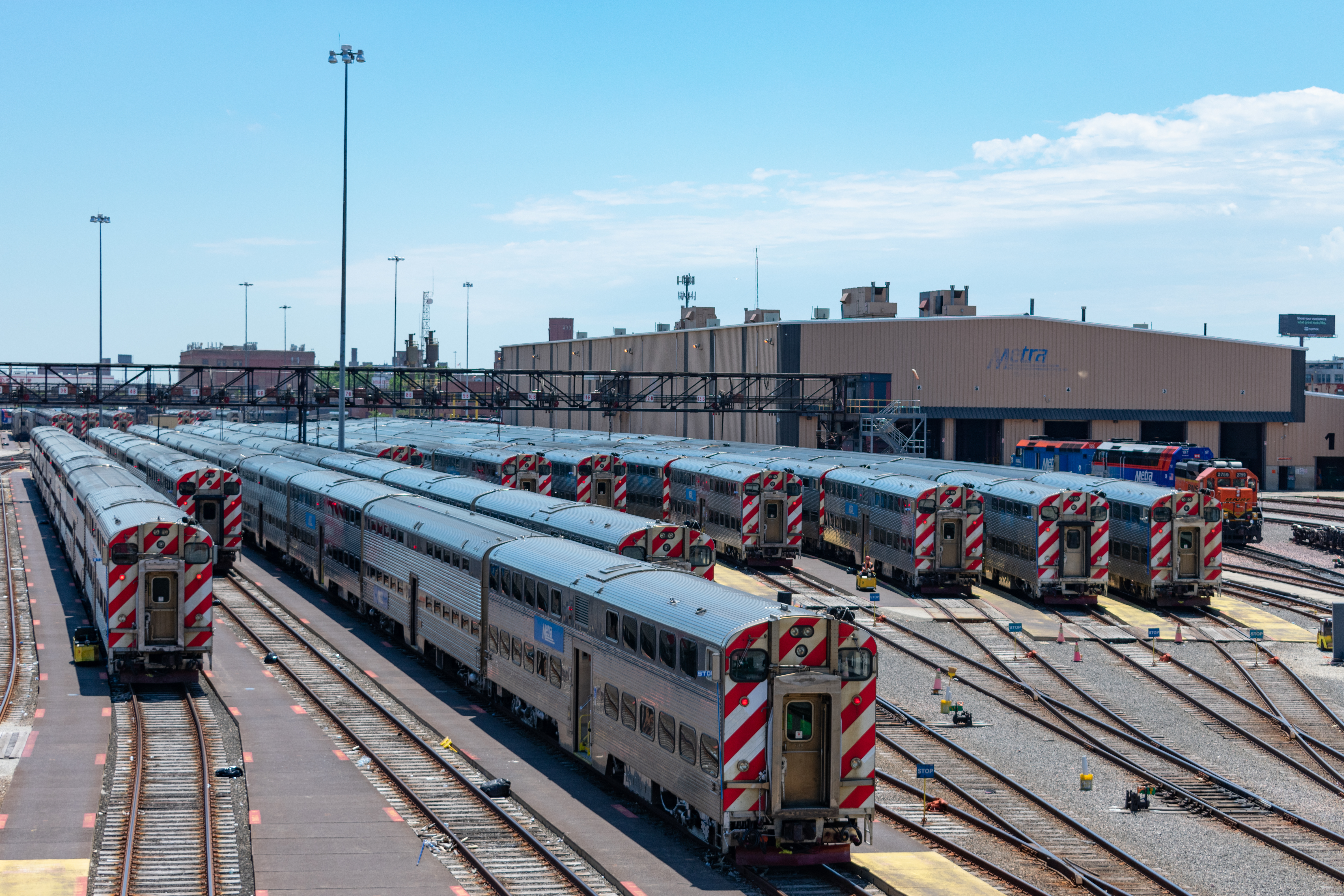 A rail yard with several silver Metra commuter trains. There are short service buildings in the distance.