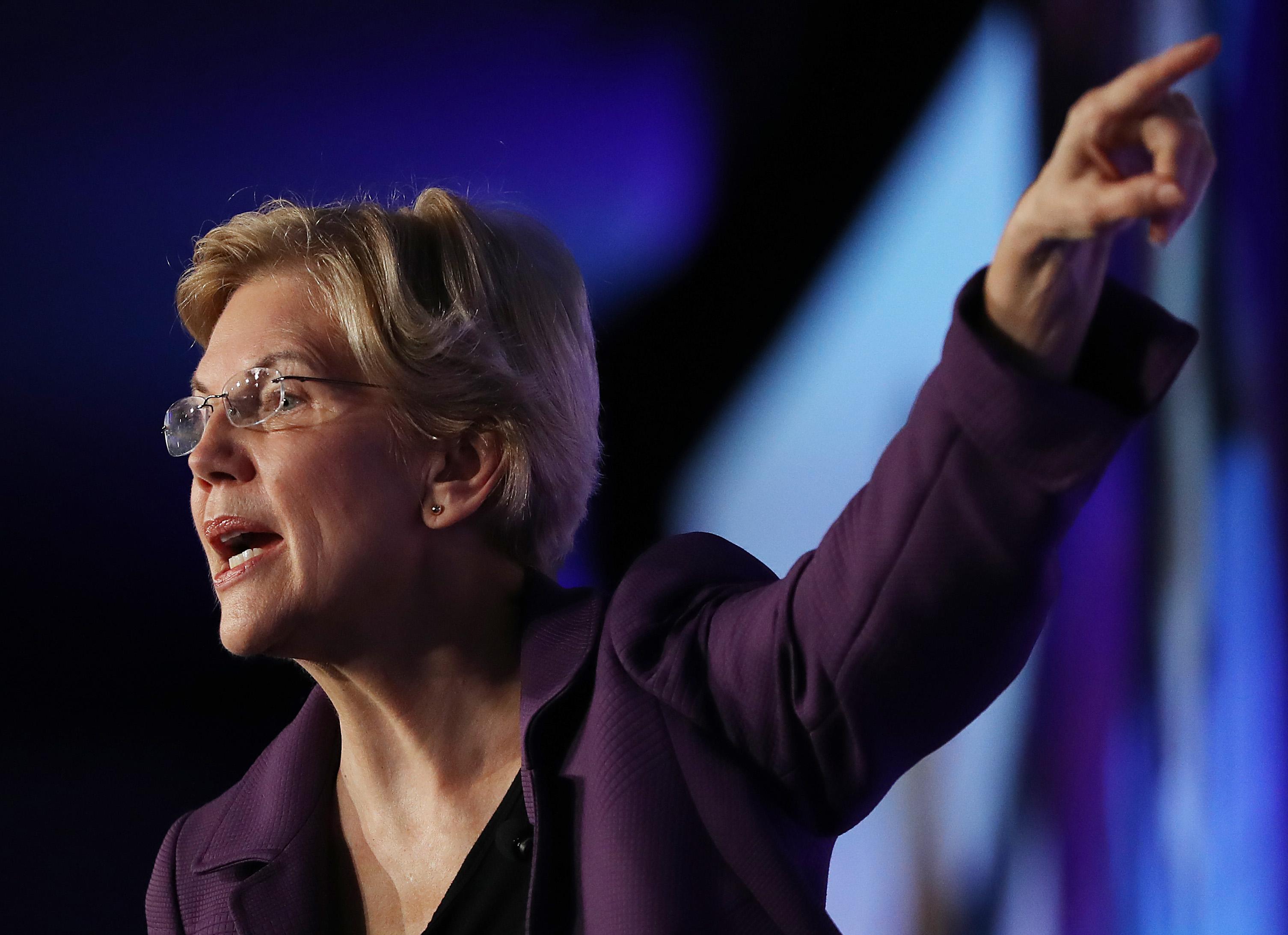 Senator Elizabeth Warren speaking and pointing from onstage.