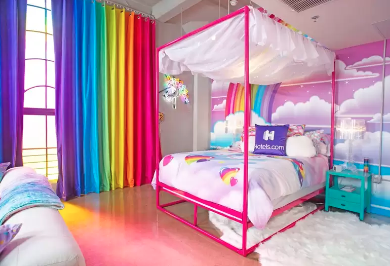 A rainbow-colored room with a hot pink four-poster bed. A vinyl wall wrap behind the bed shows clouds and a rainbow on the backdrop of a pink sky.