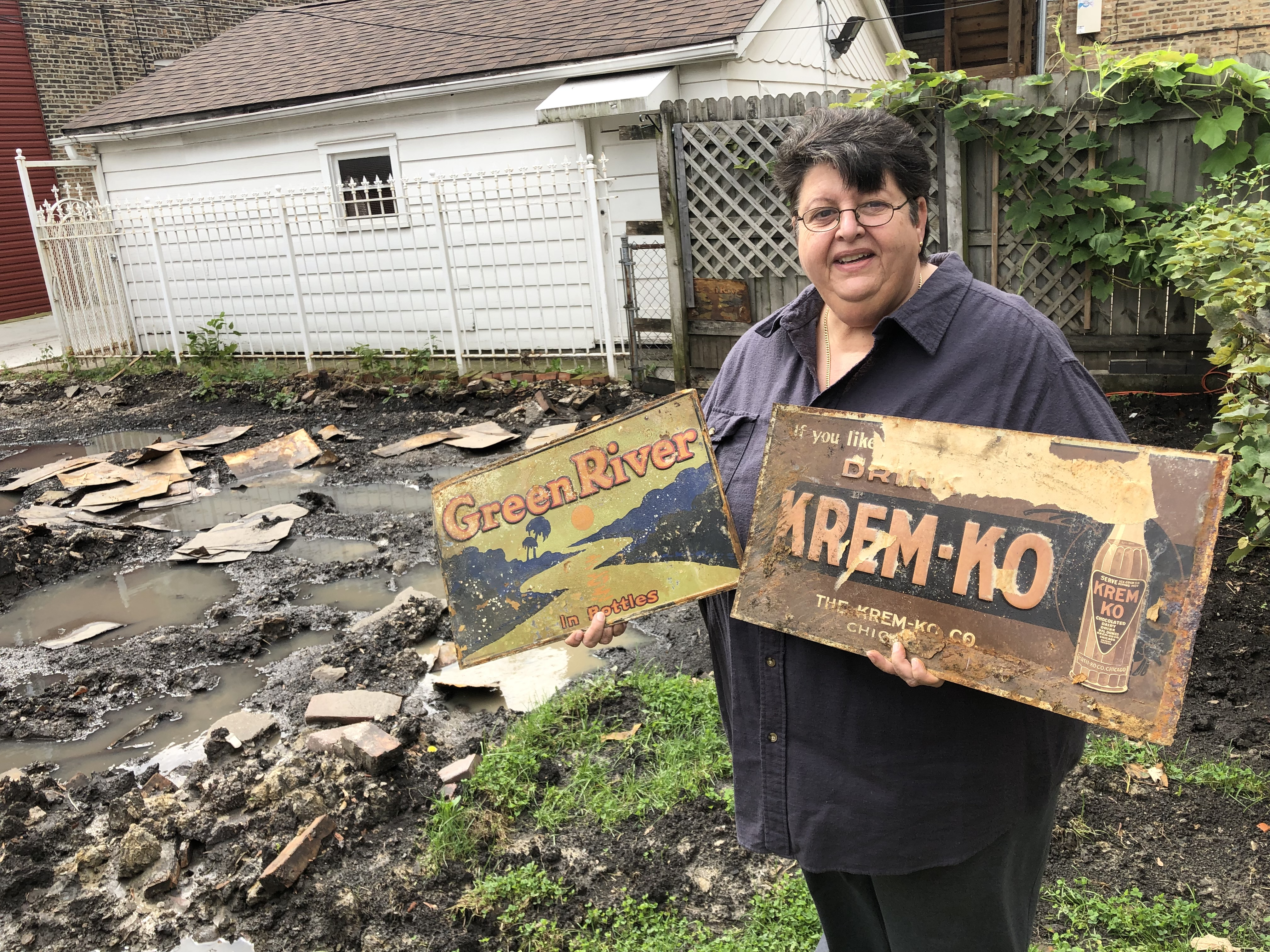 Soraya Zamora displays two of the old metal advertising signs she found under her garage.