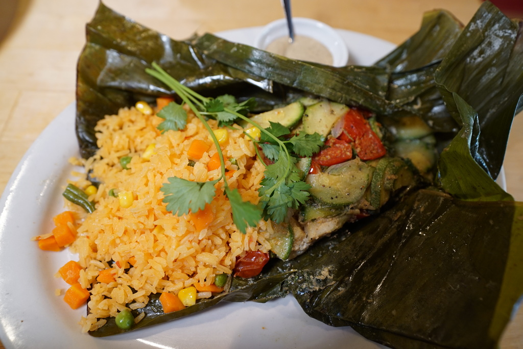 Cod in plantain leaf with pumpkin seed sauce, cherry tomatoes, zucchini, cilantro and onion.