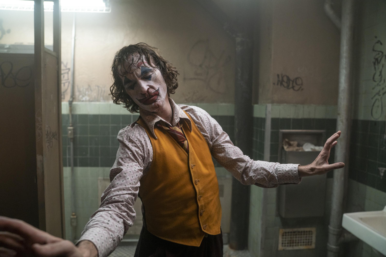 Arthur (Phoenix), in clown make-up, dances in a public restroom.