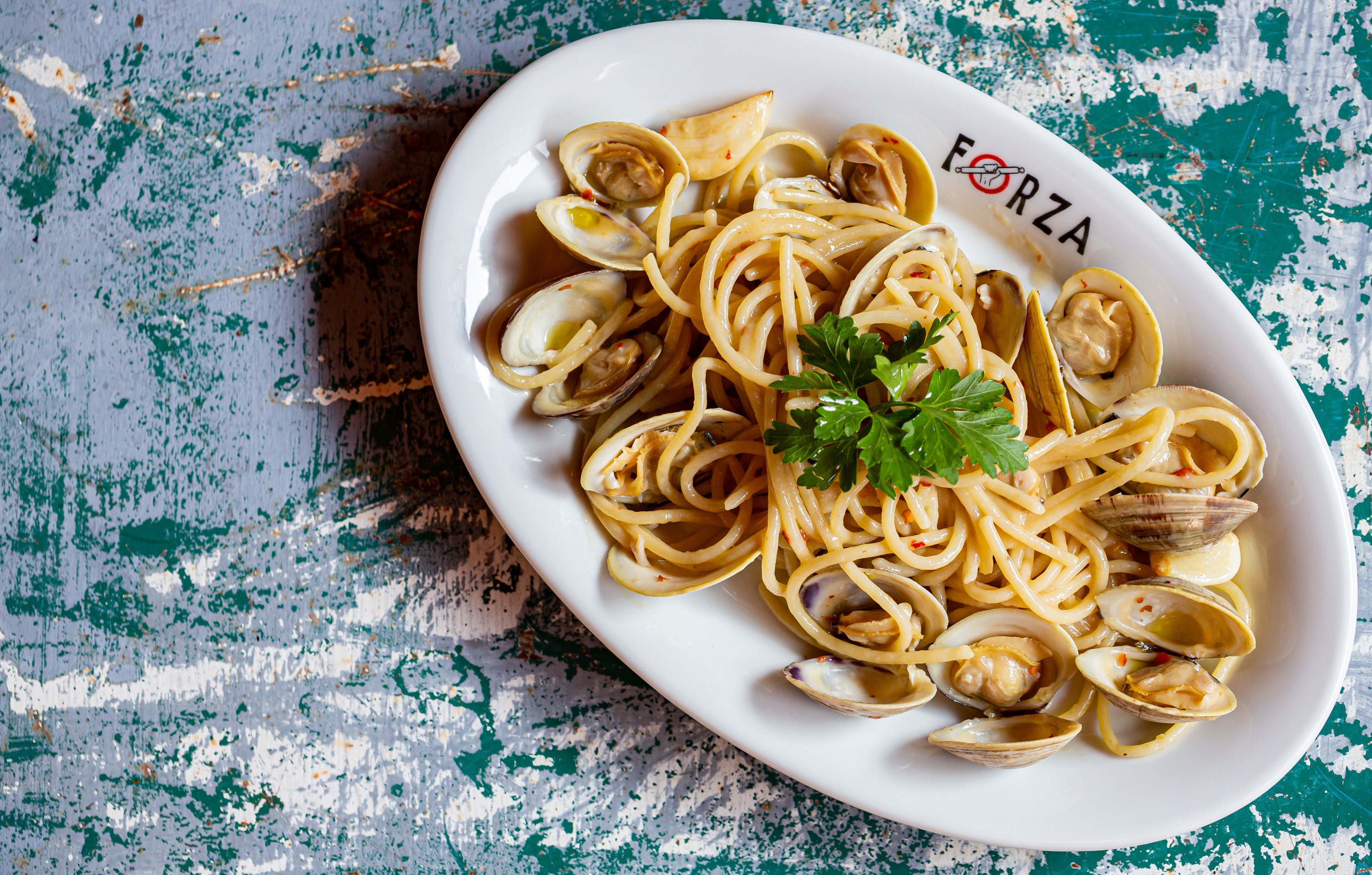 Vongole with clams on a white Forza plate atop a green and white painted table
