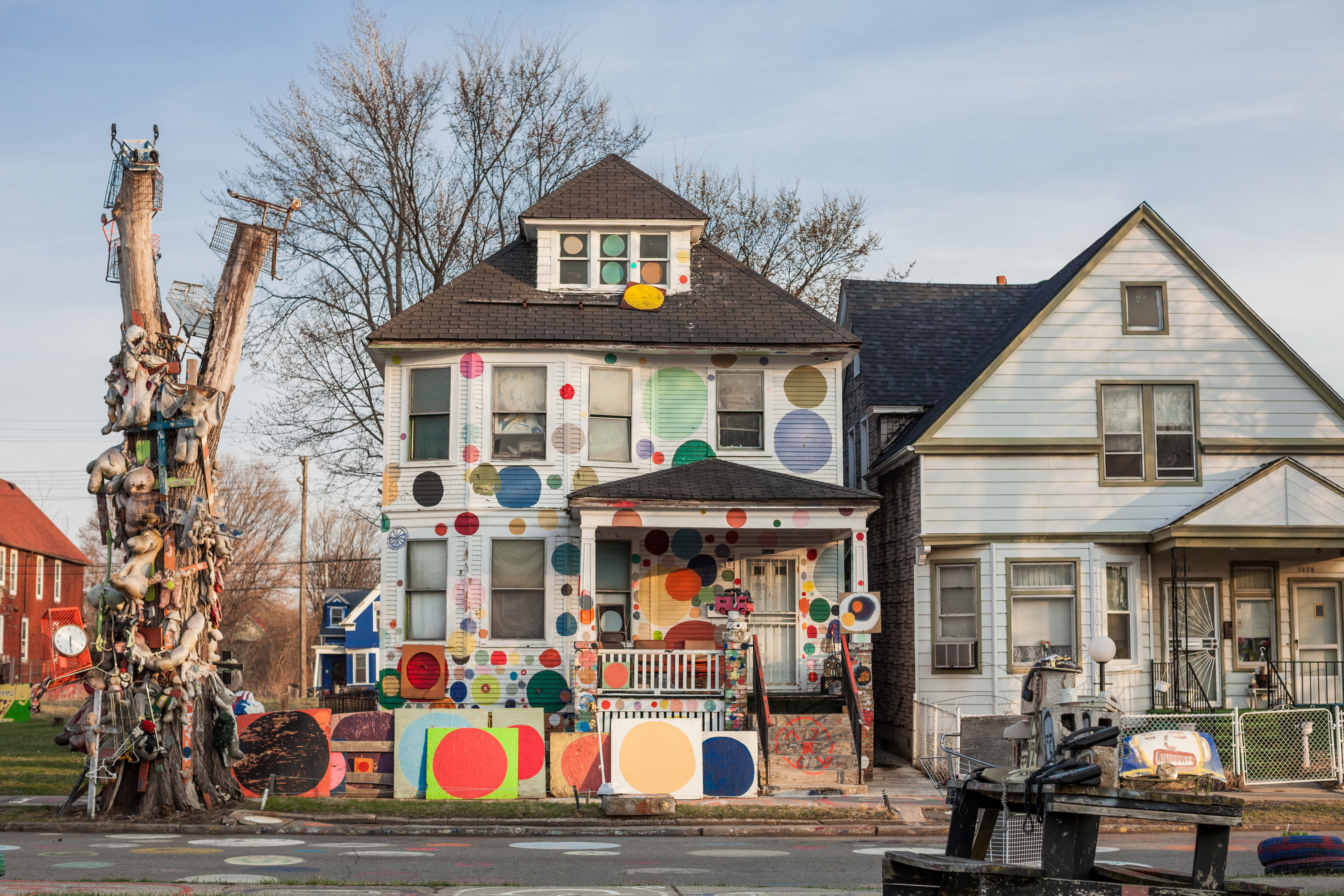 An old white foursquare house with with rainbow colored dots of different sizes painted on the siding and different found objects hanging off a dead tree next to the street.