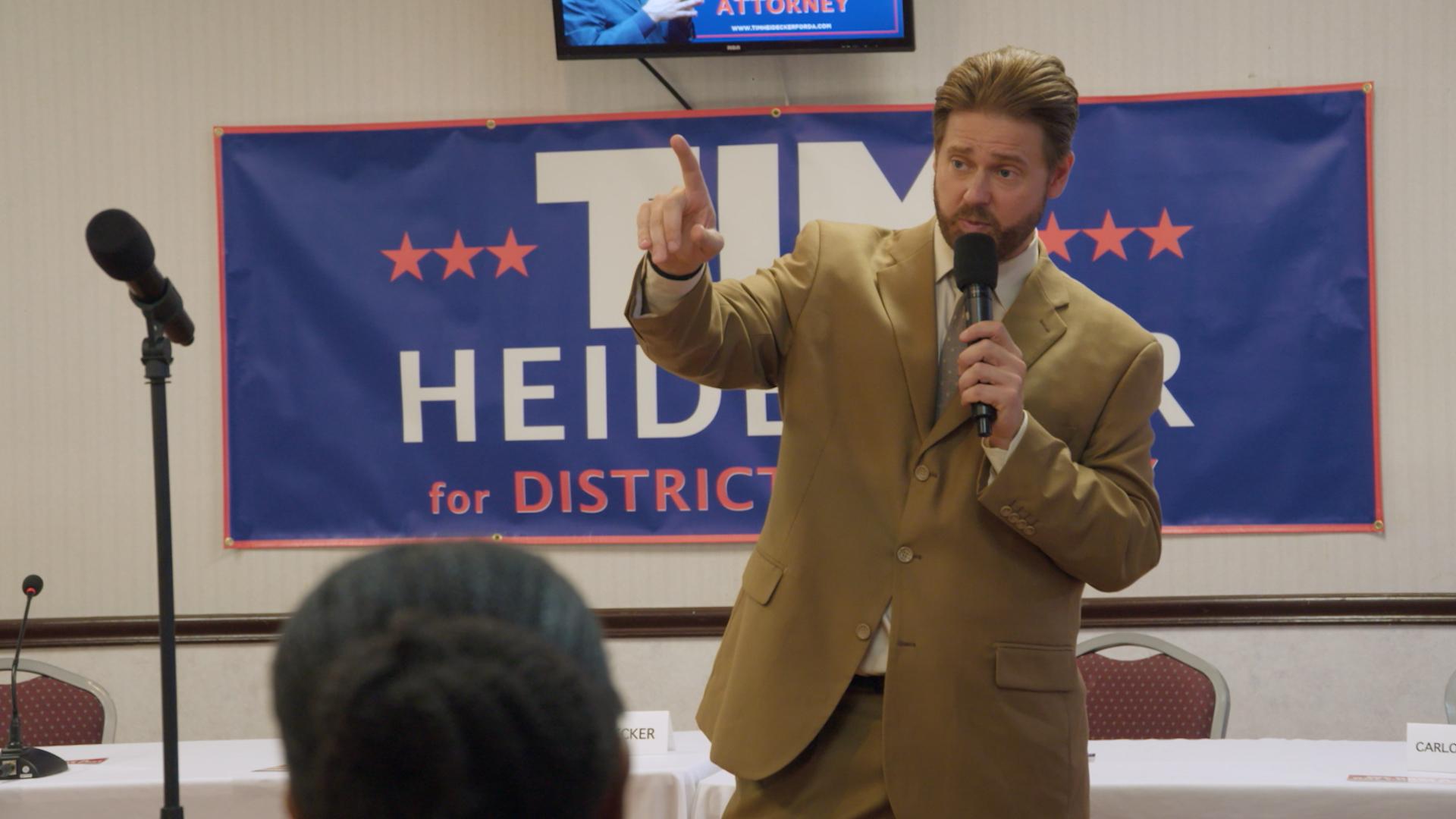Tim Heidecker gives a speech in front of a Tim Heidecker election banner