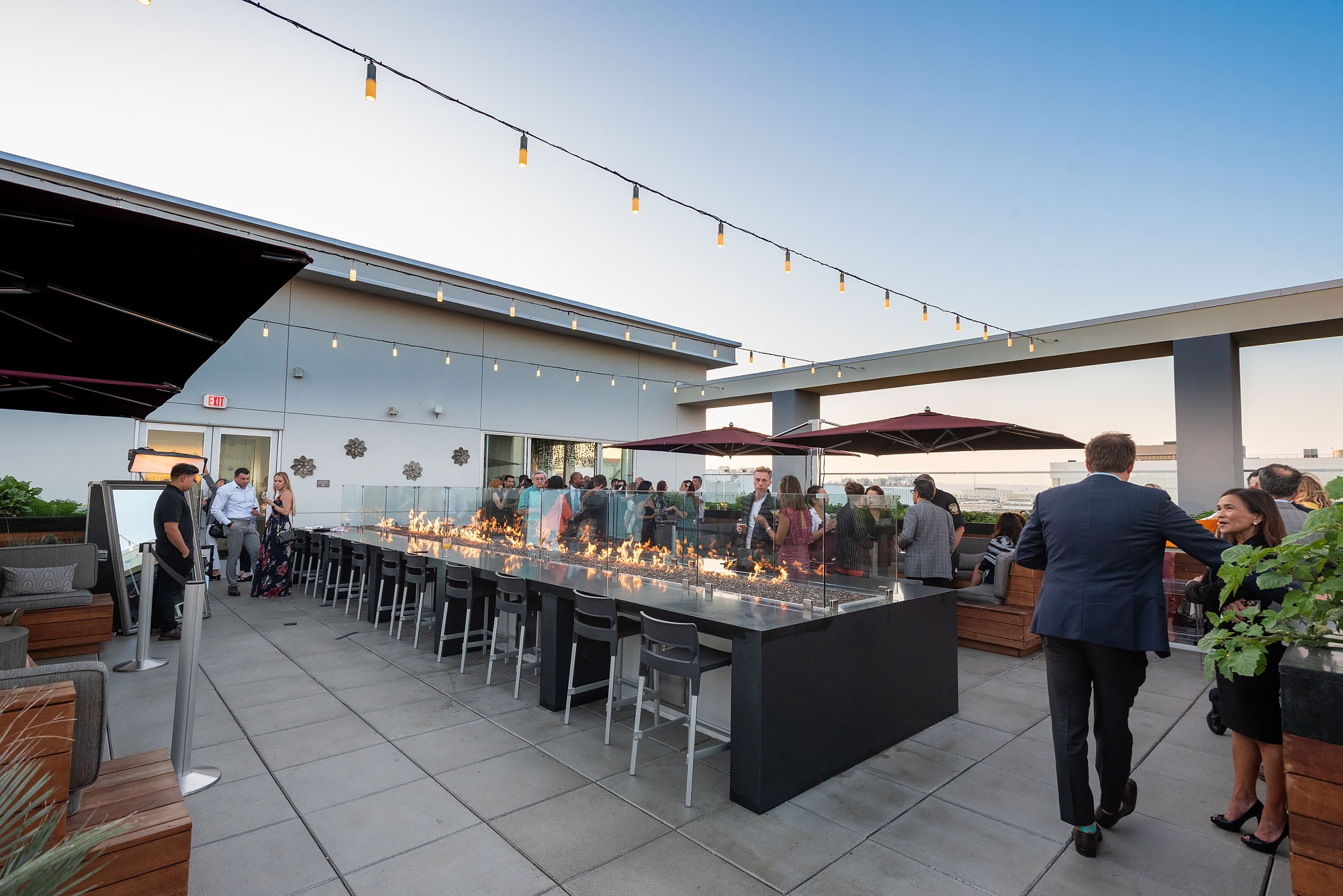 Rooftop bar with outdoor fire, umbrellas, and hanging lights.