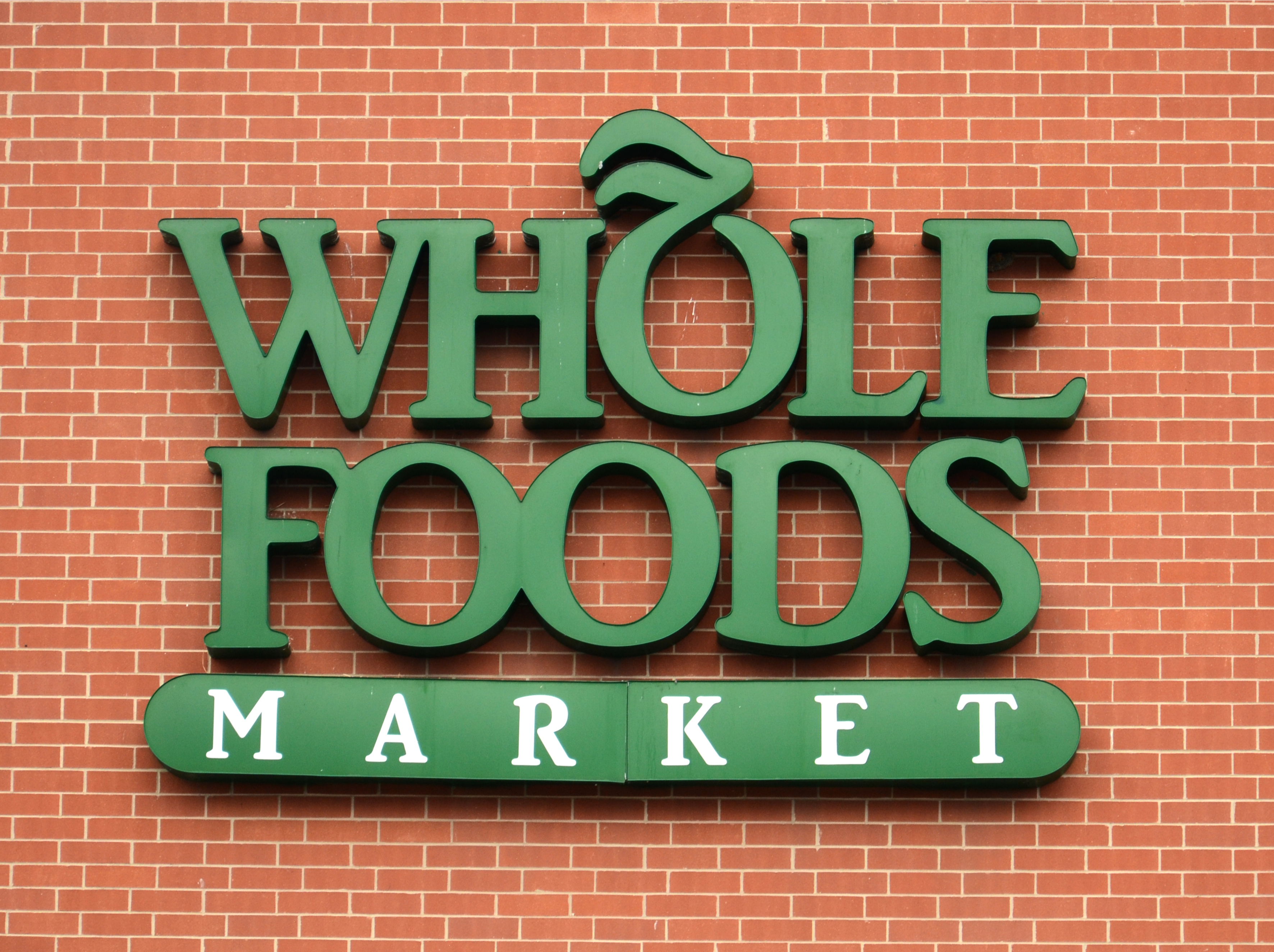 The Whole Foods Market logo shown against a brick background.