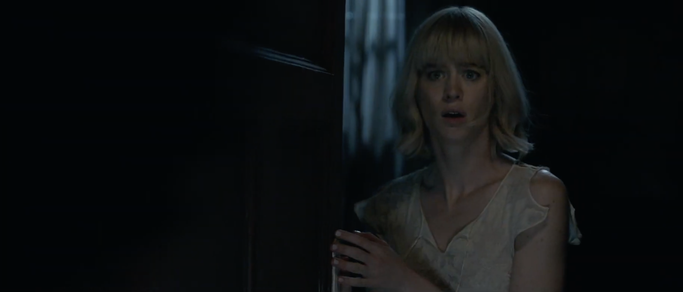 mackenzie davis in a nightgown, looking absolutely shocked, opening a door