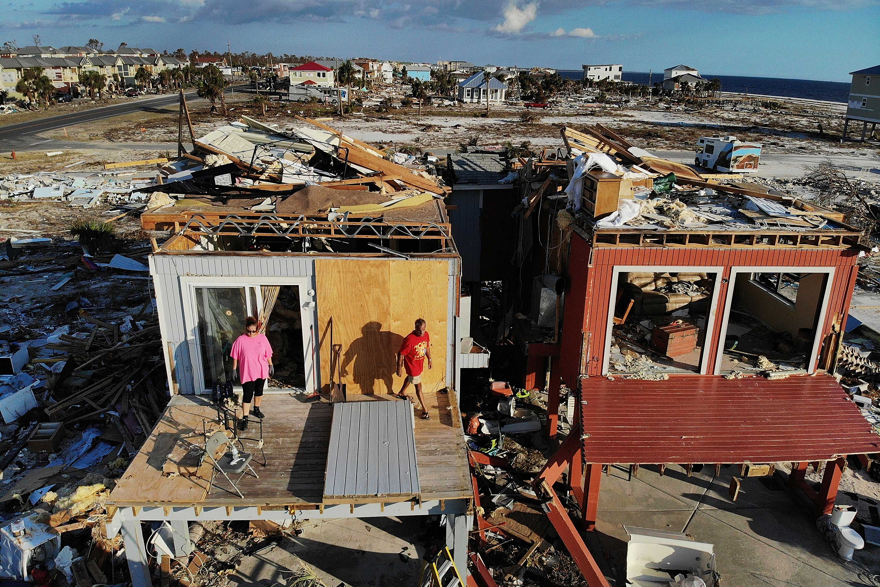 A man and woman stand in front a house missing its roof.