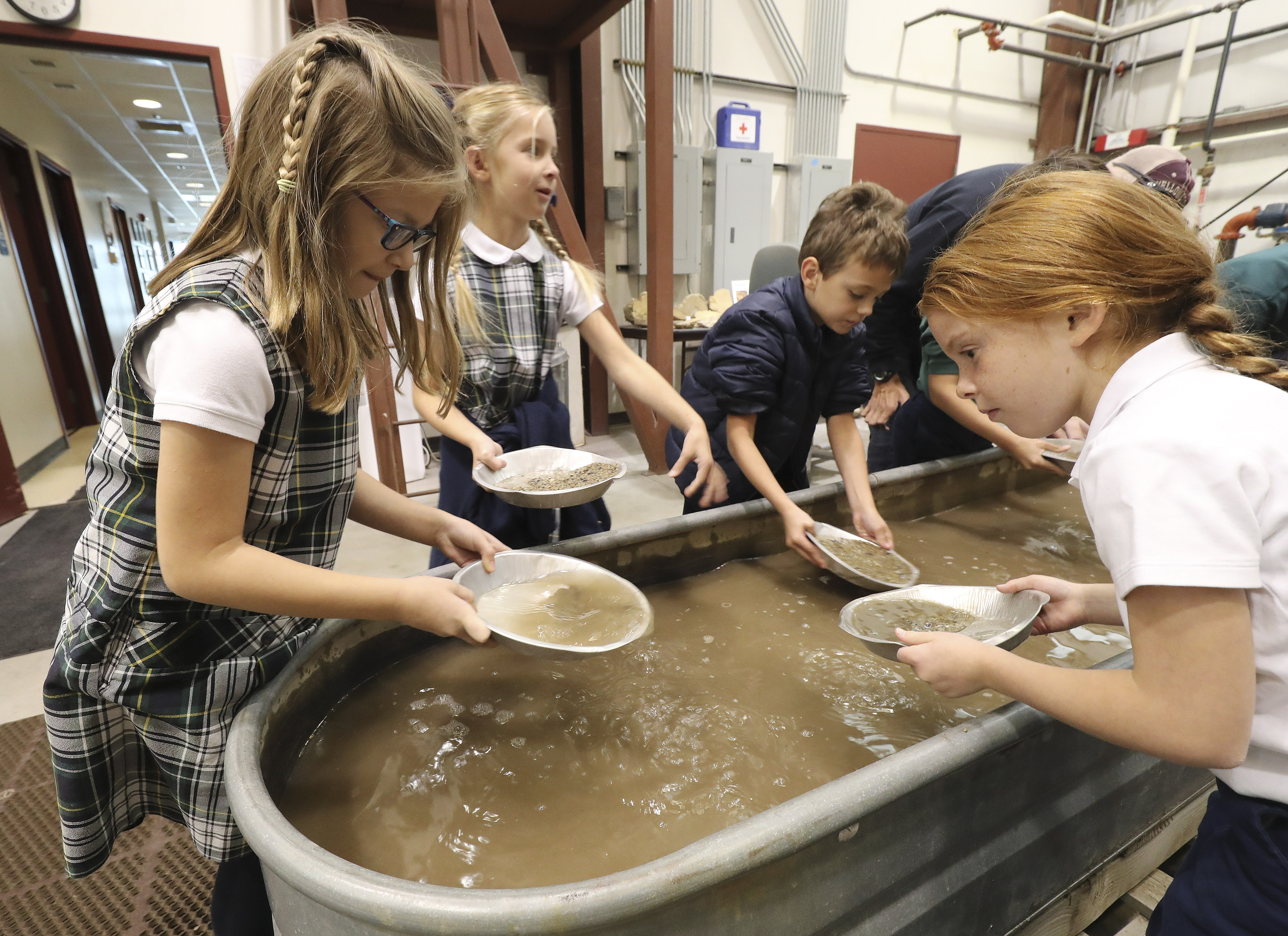 J.E. Cosgriff Memorial Catholic School students Mila Paulos, Samantha Evans, Eli Huebel and Evie Gardner pan for pyrite during Earth Science Week at the Utah Geological Survey's Core Research Center in Salt Lake City on Wednesday, Oct. 9, 2019. More than 600 elementary-age students from schools along the Wasatch Front will visit the center this week for hands-on learning opportunities as they explore rocks and minerals, fossils, dinosaurs and geologic processes.
