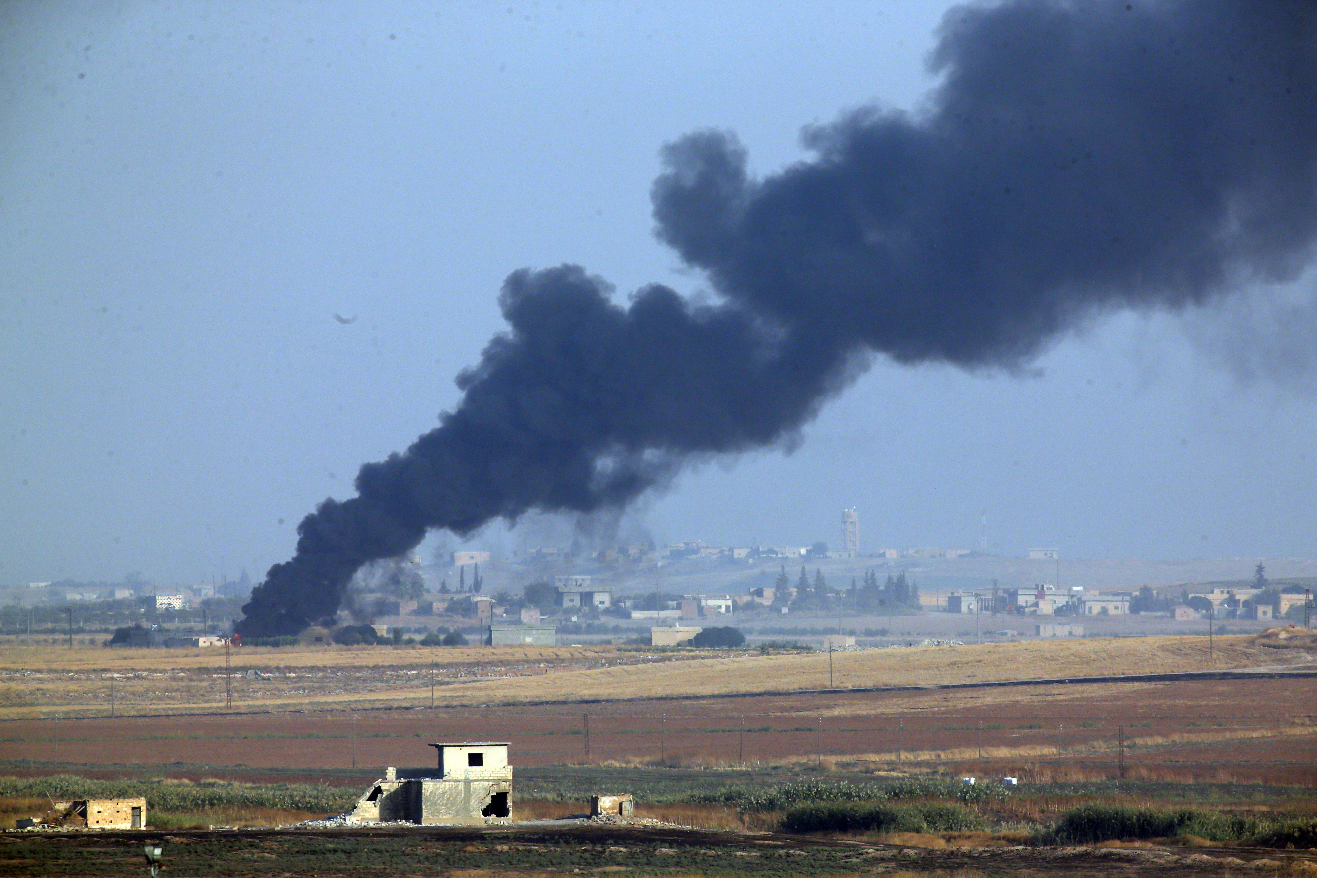 Smoke billows from a fire inside Syria during bombardment by Turkish forces on Wednesday.