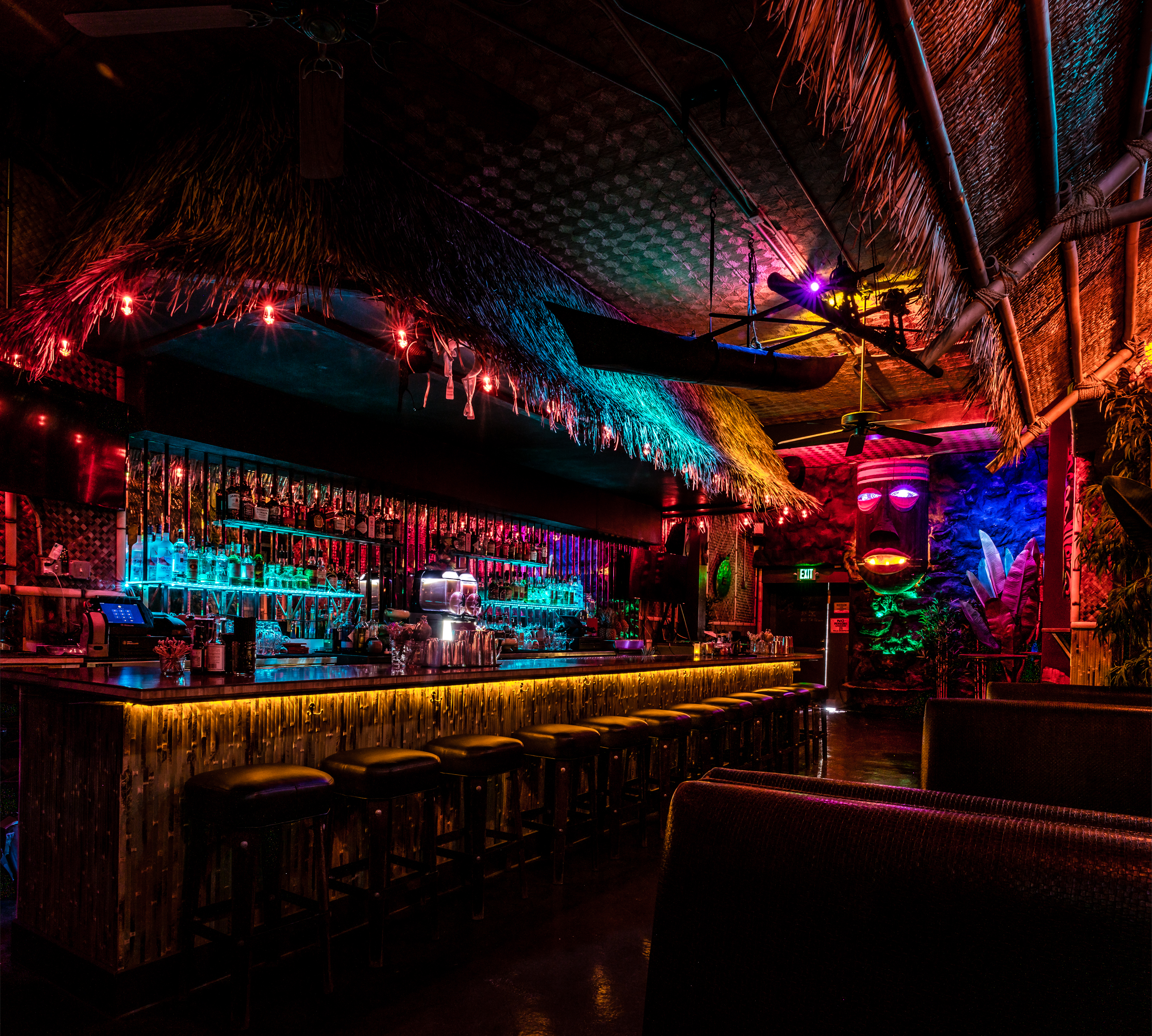 Inside the bamboo hut, where a thatched bar is lit by multi-color lights