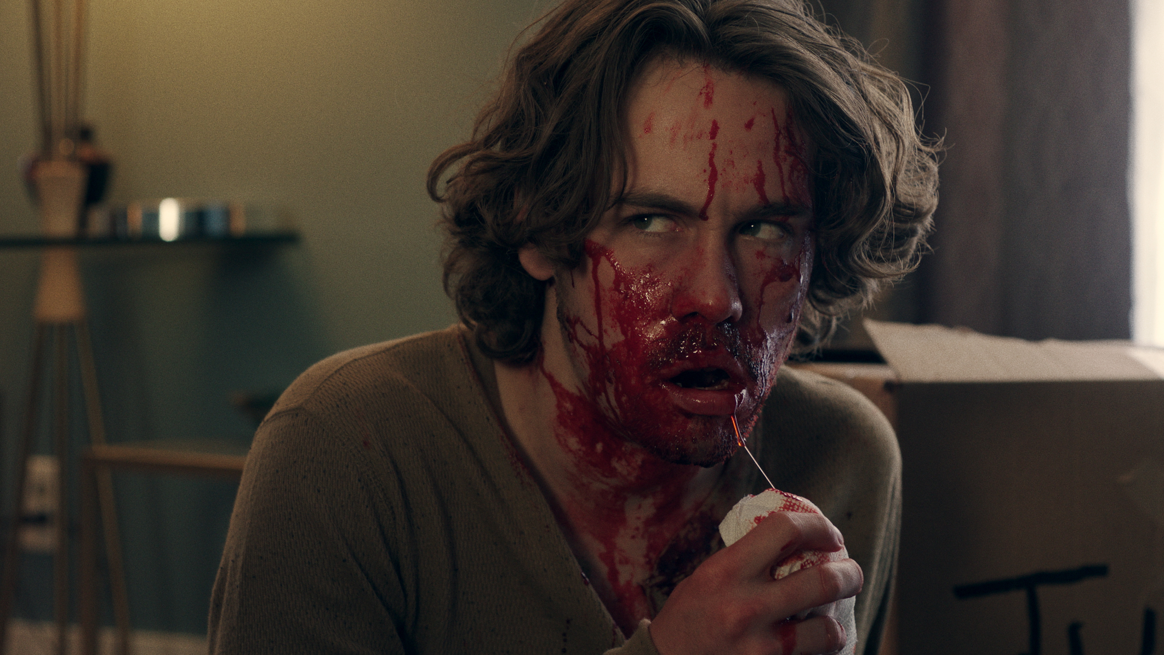 a man with a bloody face takes a sip from a milkshake