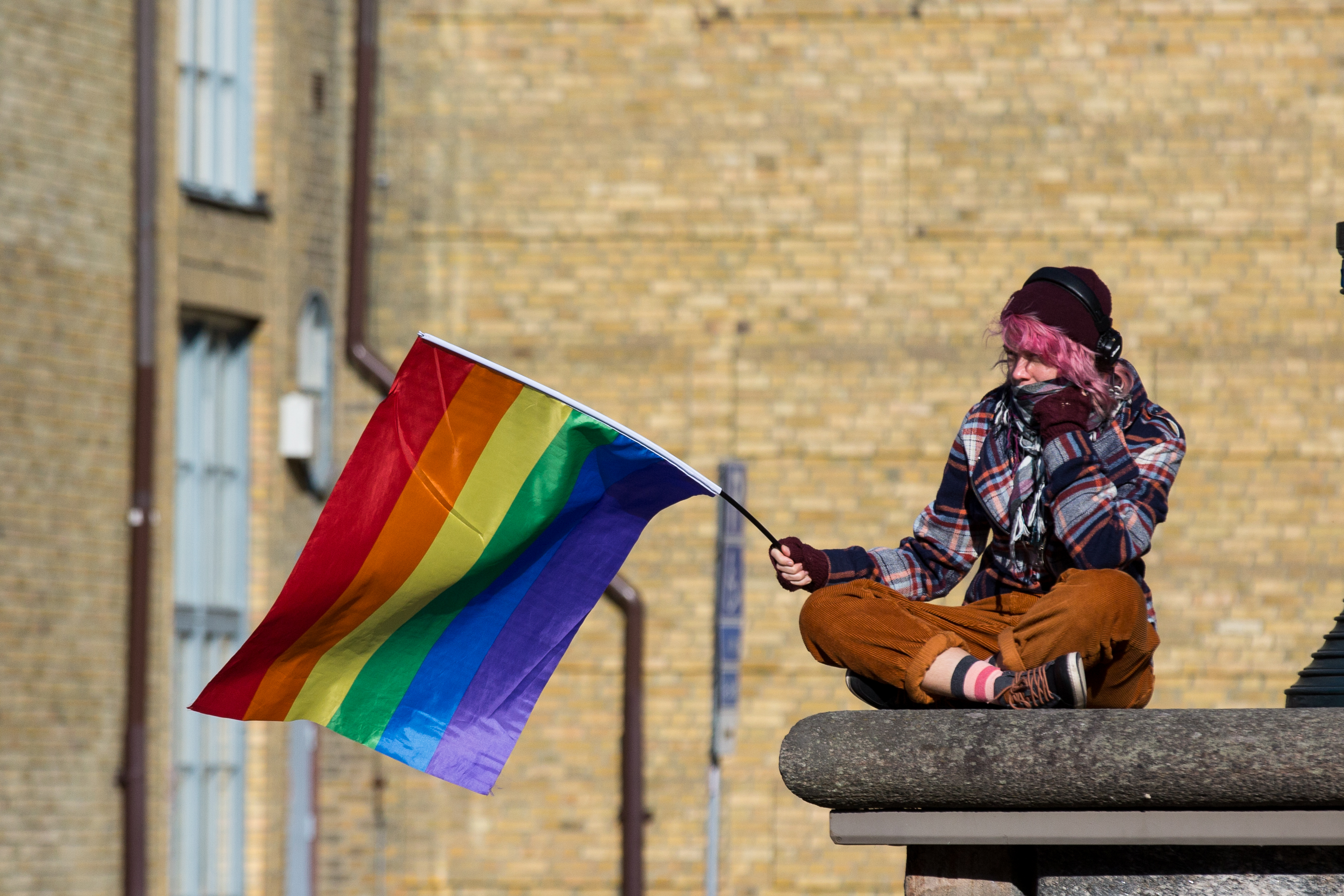 A woman siting on a building ledge holds an LGBT rainbow flag on a stick.