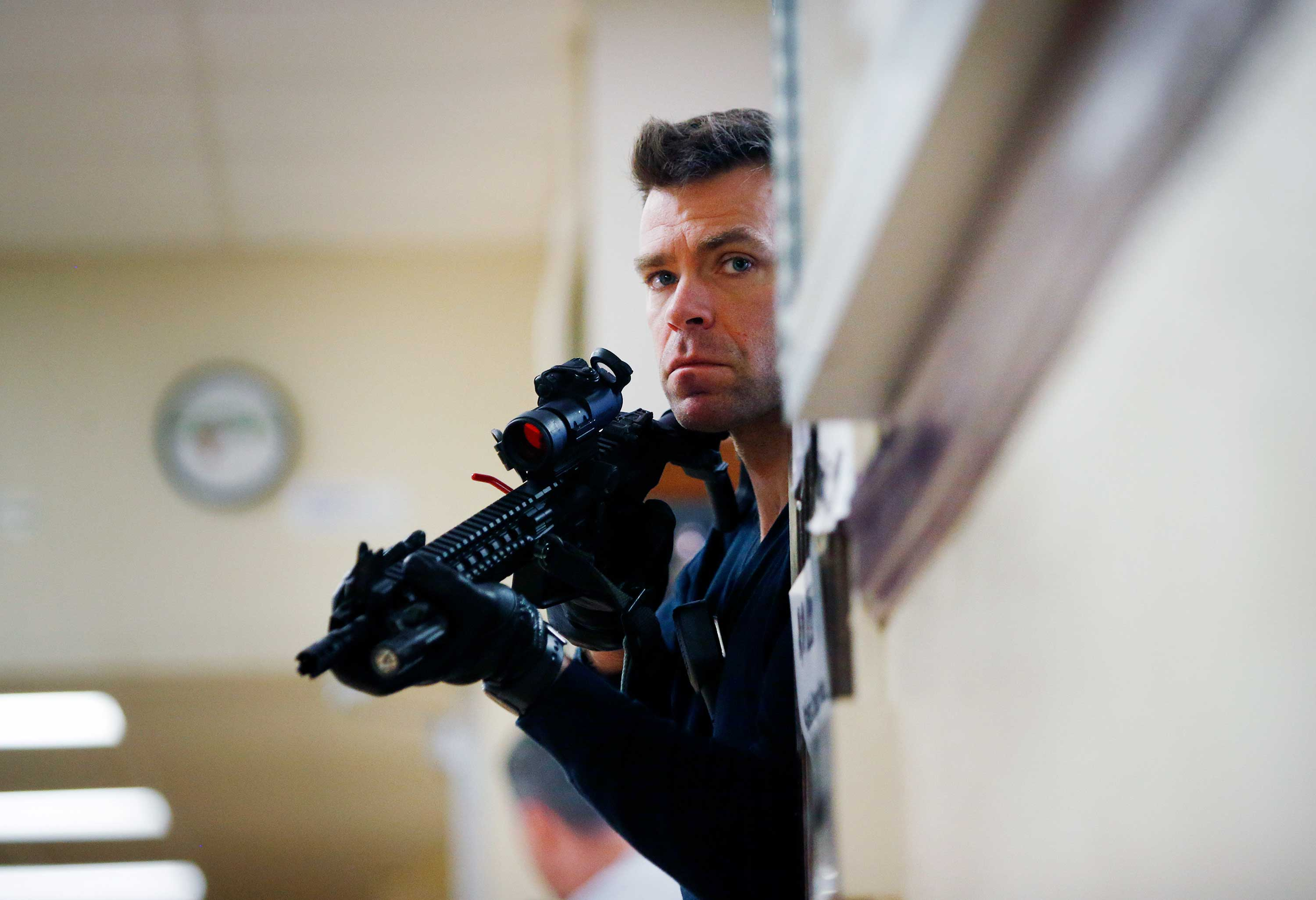 A law enforcement officer holding a gun secures a hallway during a regional active shooter training drill.