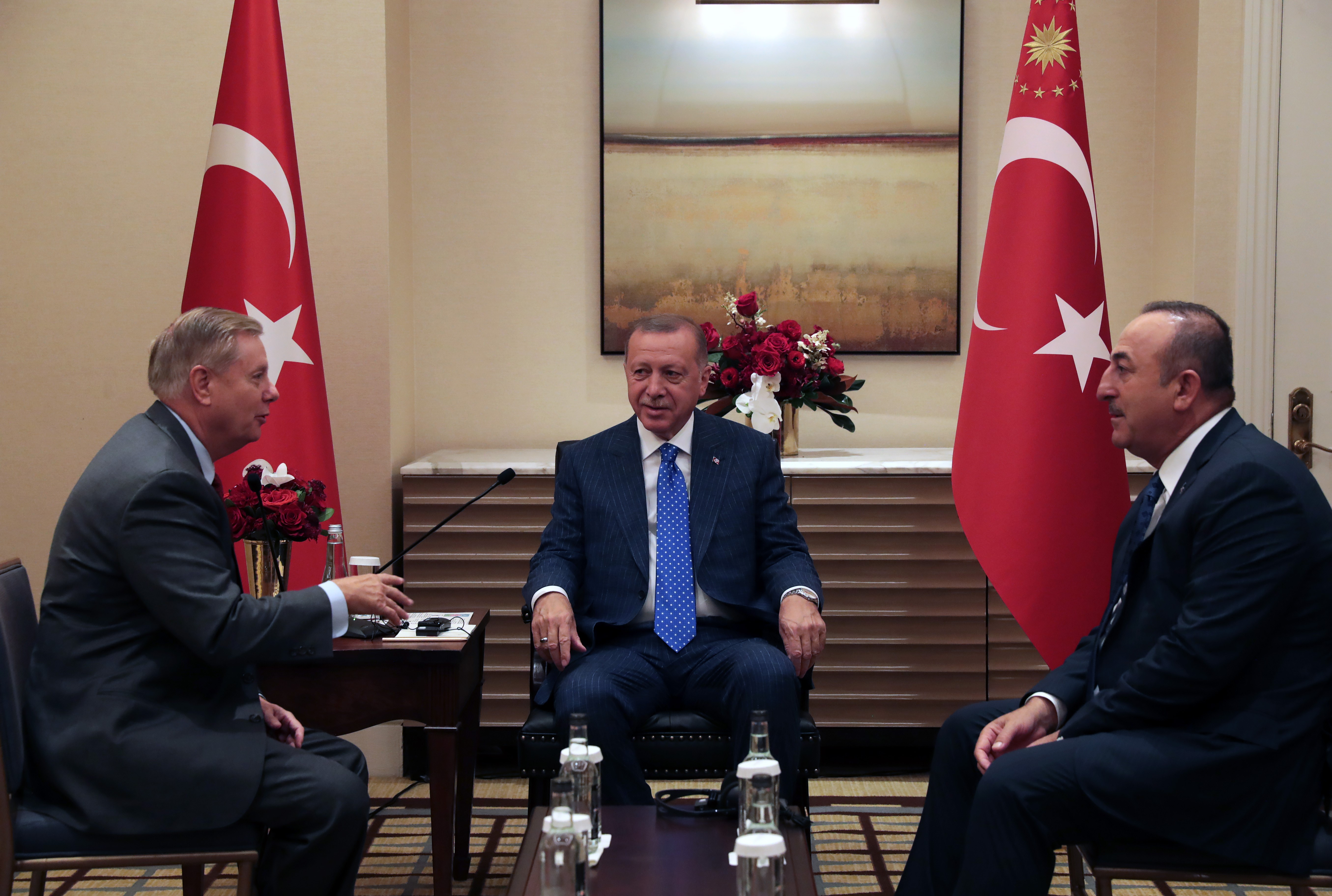 President of Turkey Erdogan in New York alongside Lindsey Graham, seated with Turkish flags behind them.
