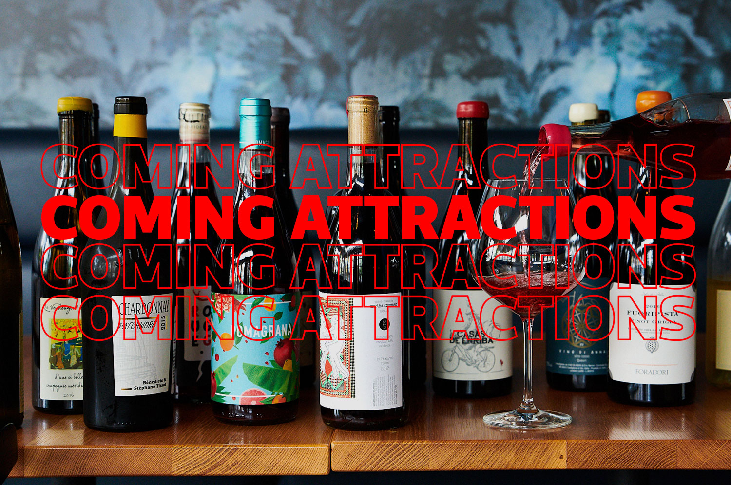 Bottles of wine on a table in front of a graphic that says Coming Attractions four times