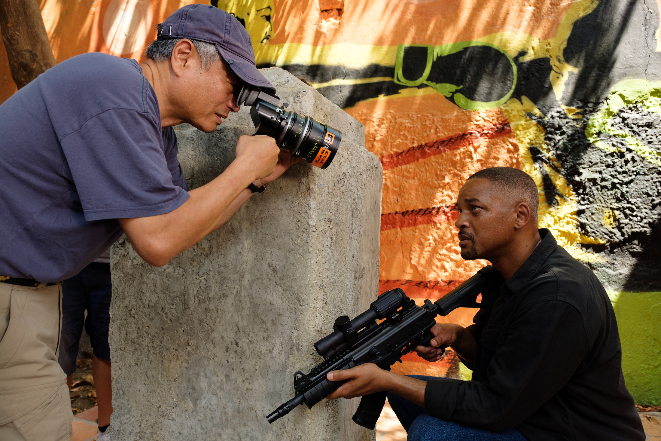 Ang Lee lines up his shot with a viewfinder as Will Smith crouches on the ground with a semi-automatic rifle