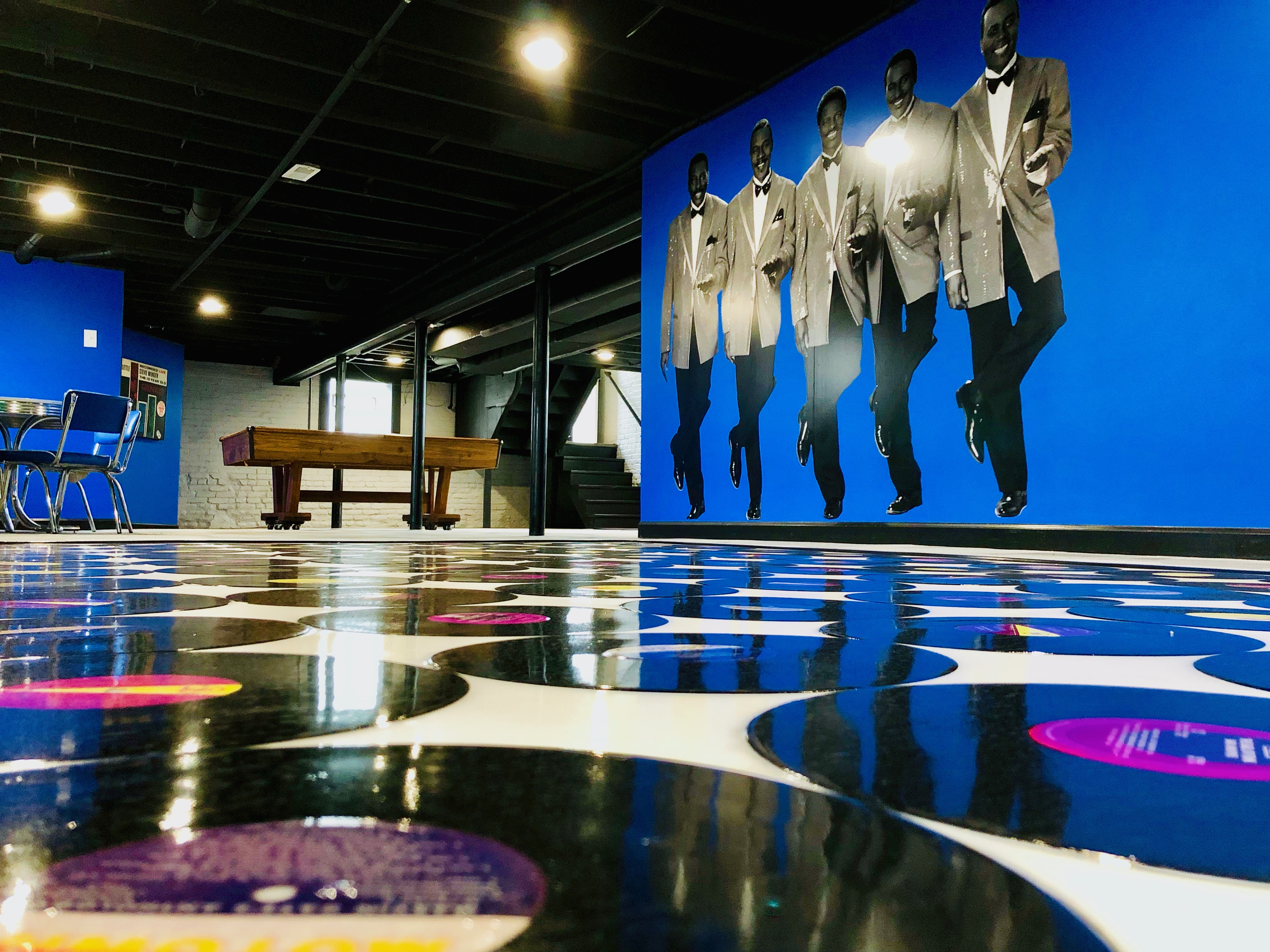 A vinyl-covered floor and a blue wall painted with five tuxedo-wearing dancers.